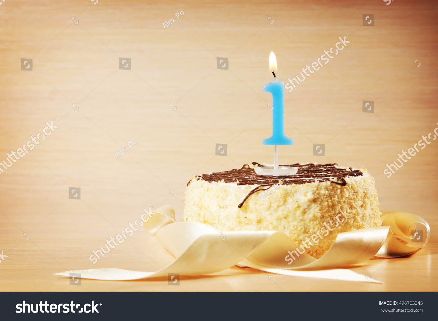 Birthday Cake With One Decorative Burning Candle Against Beige