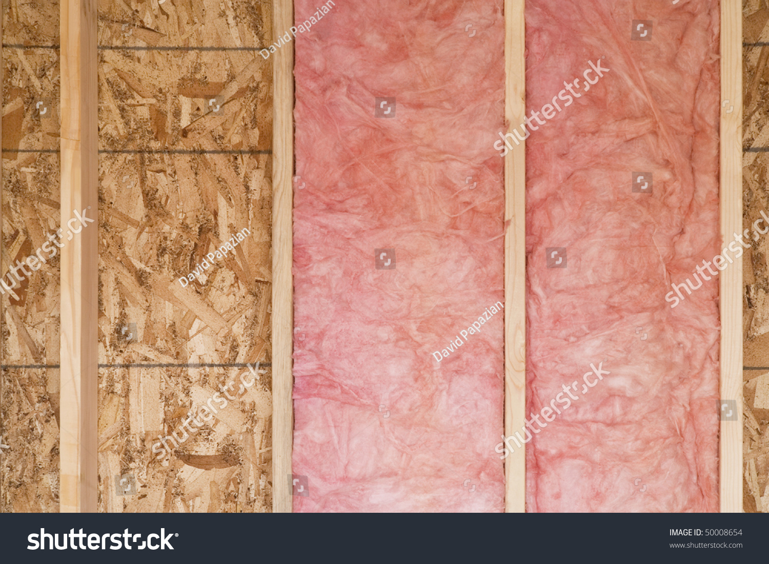 Close up of strips of pink fiberglass insulation in a wall for Fiberglass insulation sizes