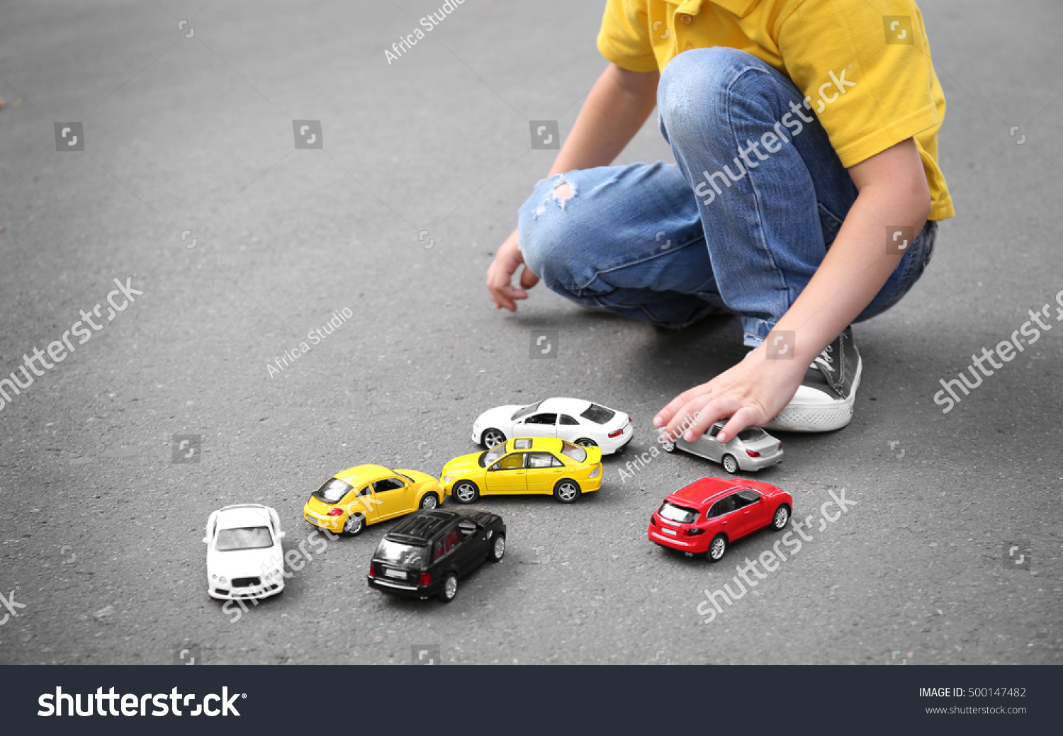 Hunting Toys For Little Boys : Little boy playing with toy cars outdoor stock photo