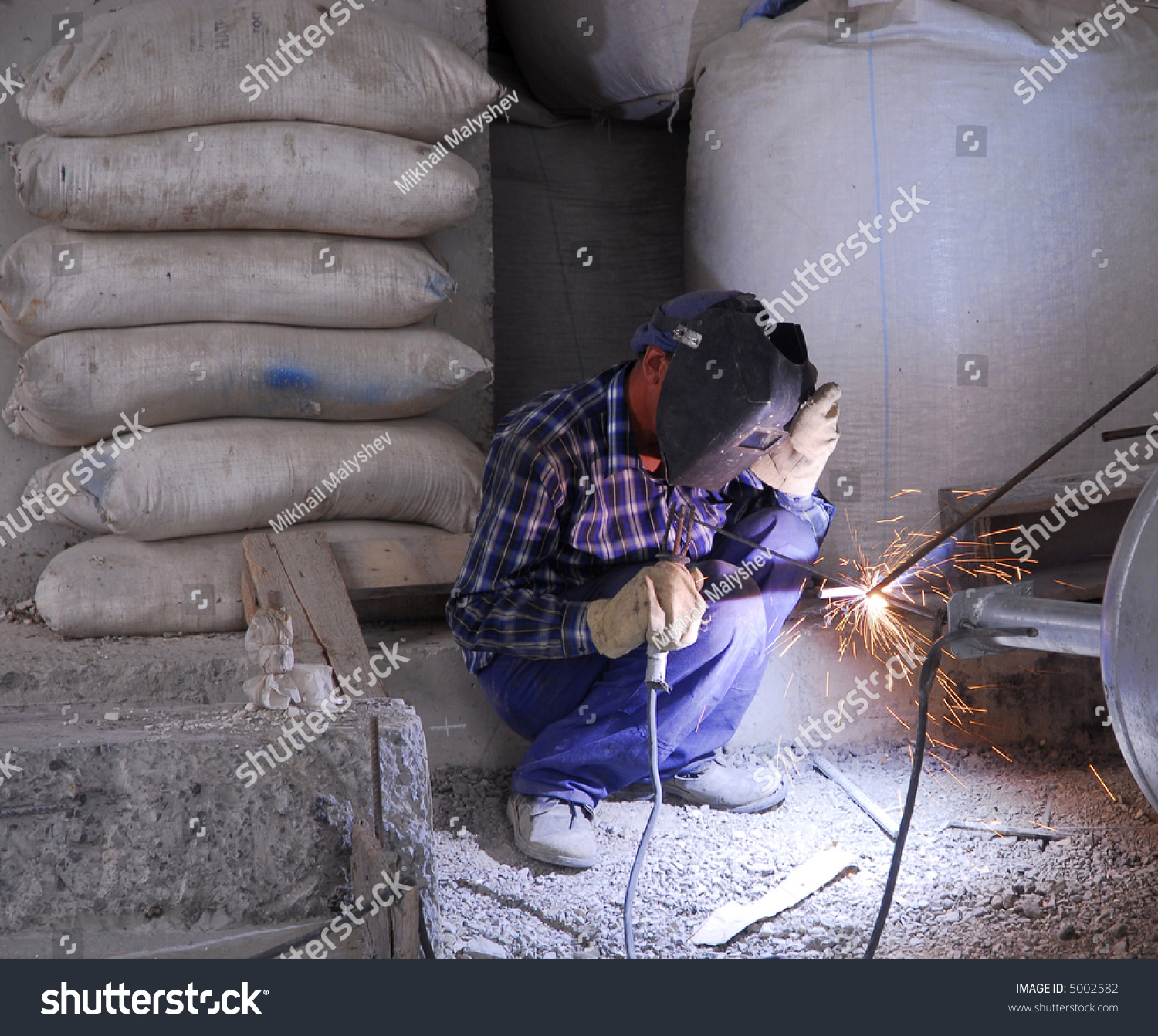 Welding operator on the floor and sparks 2 stock photo for Floor operator