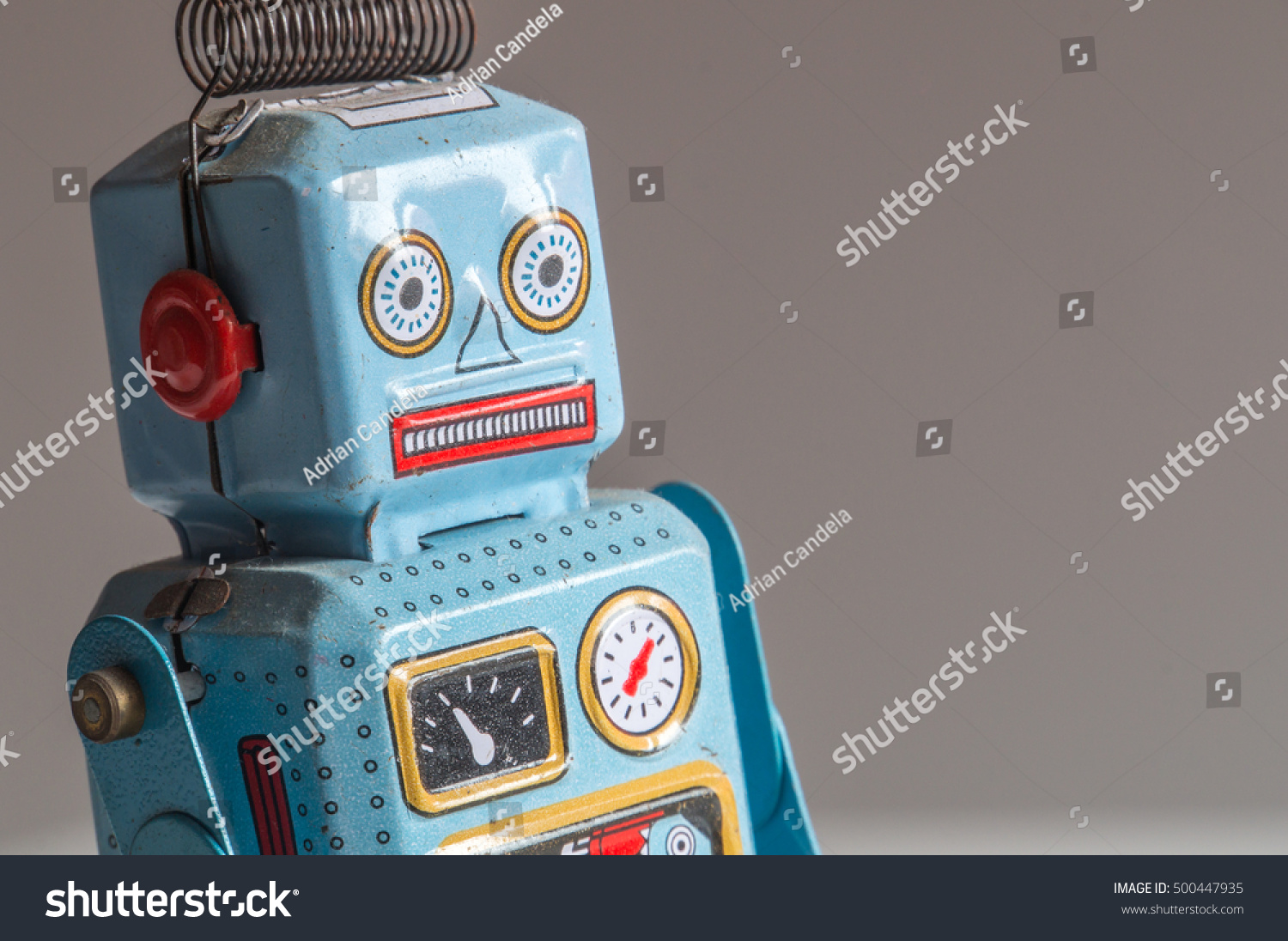 Three-quarter view of a blue and red tin robot toy's head and upper torso facing to the right on a blurred gradient background