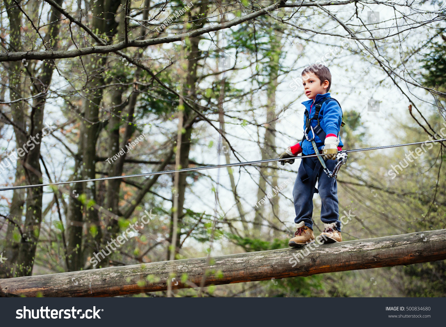 stock photo boy in harness navigating obstacle in adventure park on sunny day 500834680 boy harness navigating obstacle adventure park stock photo (edit now