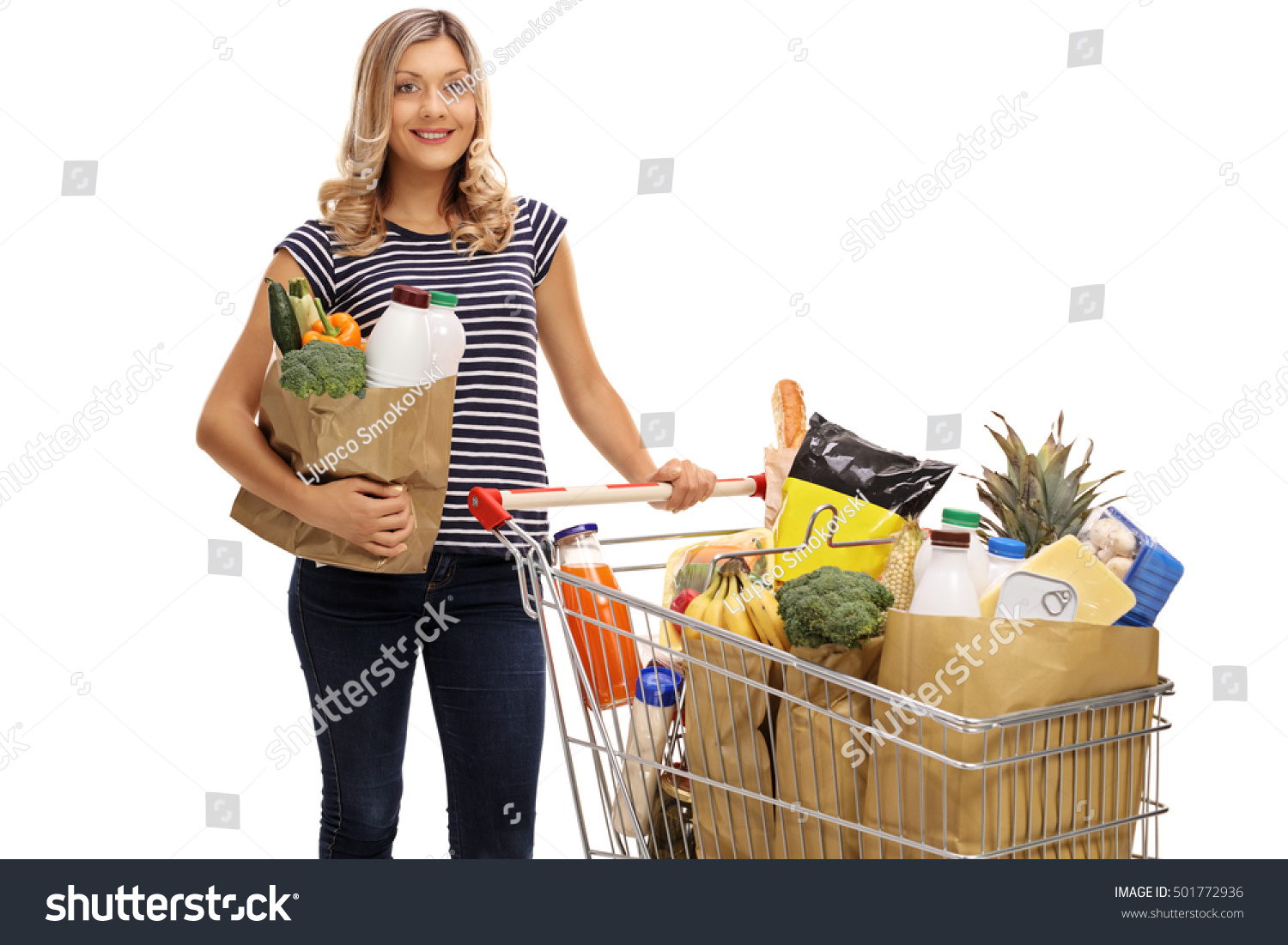 Woman posing with shopping bags isolated on white background full - Young Woman Posing With A Shopping Bag And A Shopping Cart Full Of Groceries Isolated On