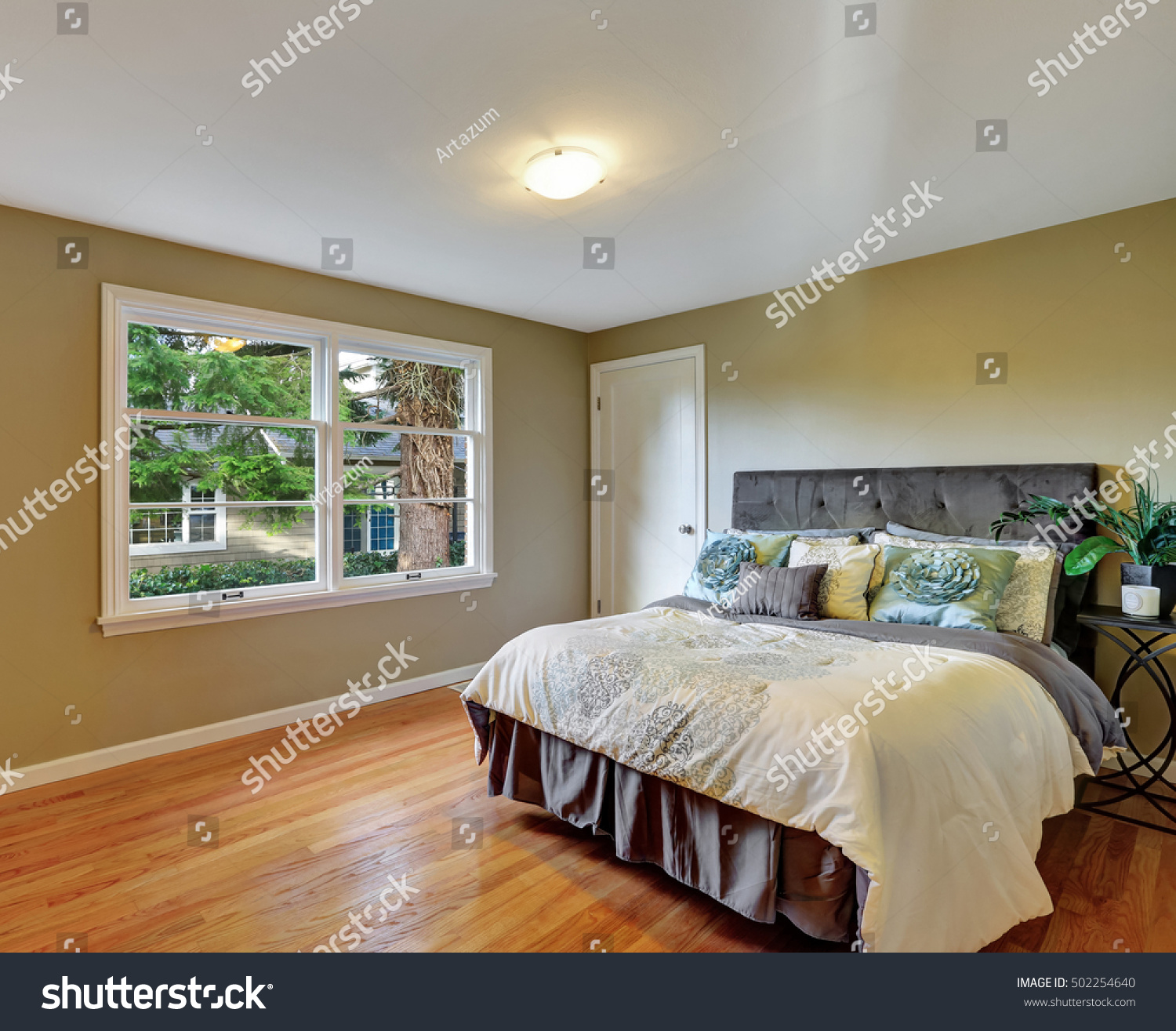 Green Bedroom Interior With Hardwood Floor And Queen Size Bed With