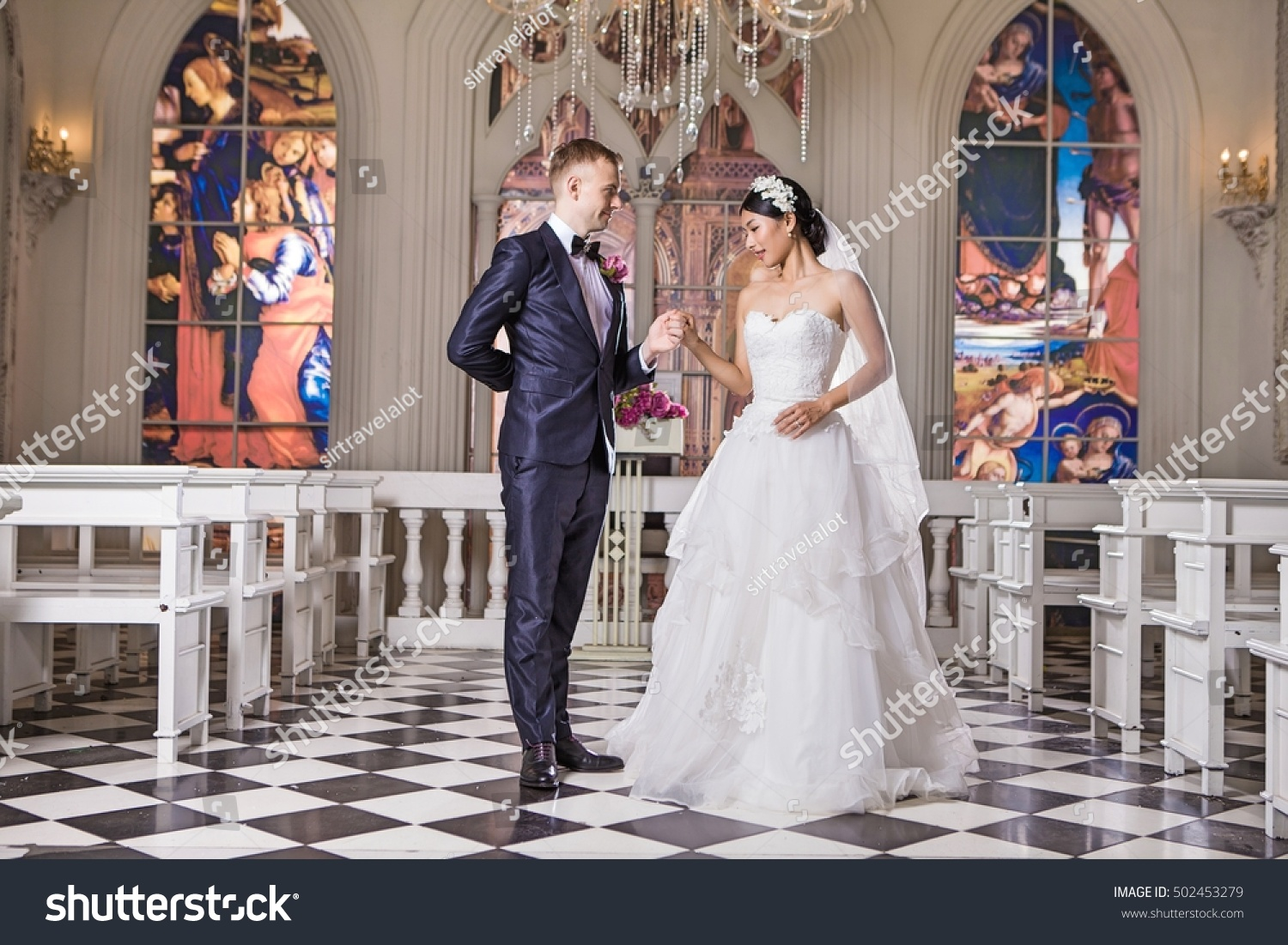 8389196f13f Side view of romantic wedding couple looking at each other in church