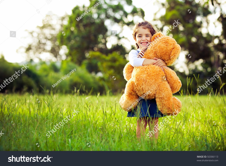 小可爱的女生站在女孩上举行大的泰迪熊-白菜草地公园图片