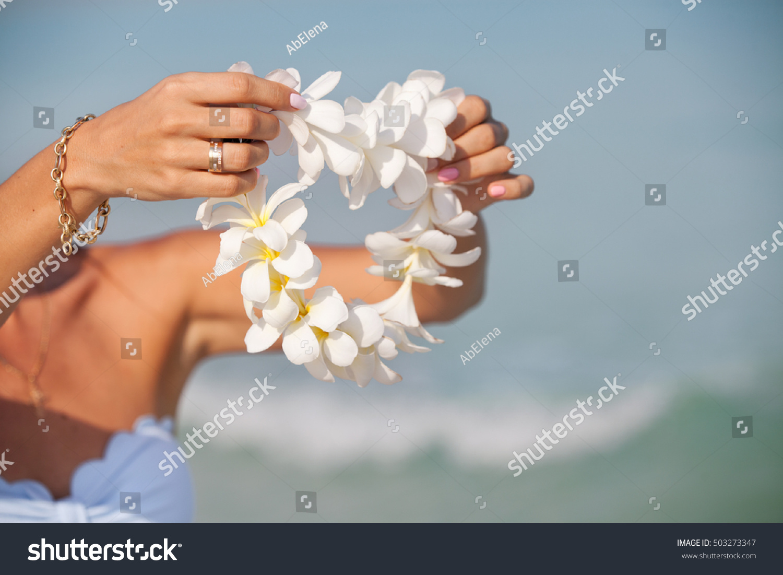 Woman hands holding flower lei garland stock photo edit now woman hands holding flower lei garland of white plumeria welcoming lei on the hawaiian island izmirmasajfo