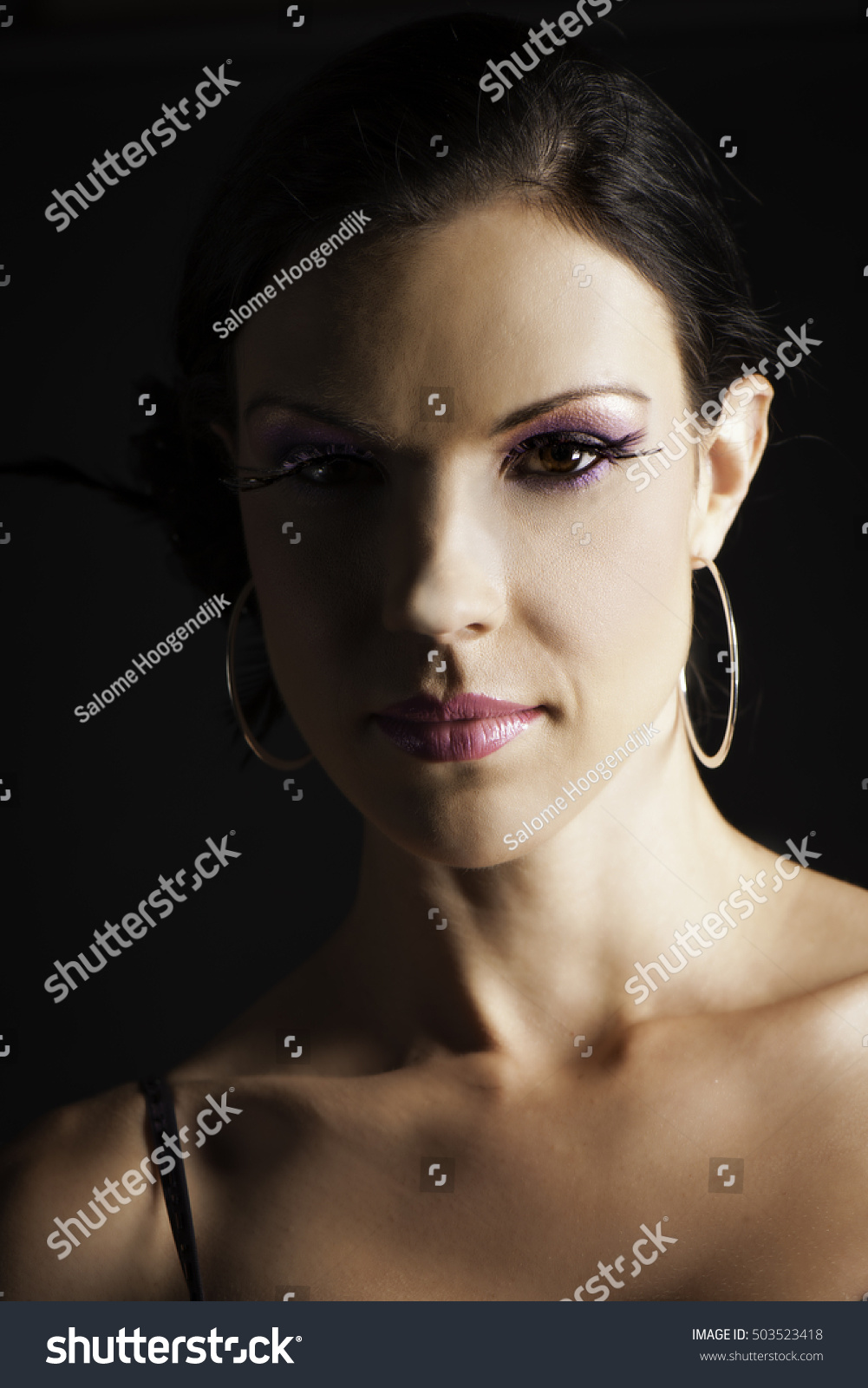 4c3892a5978 Portrait of beautiful dark haired woman wearing purple makeup with  elaborate black false eyelashes and silver