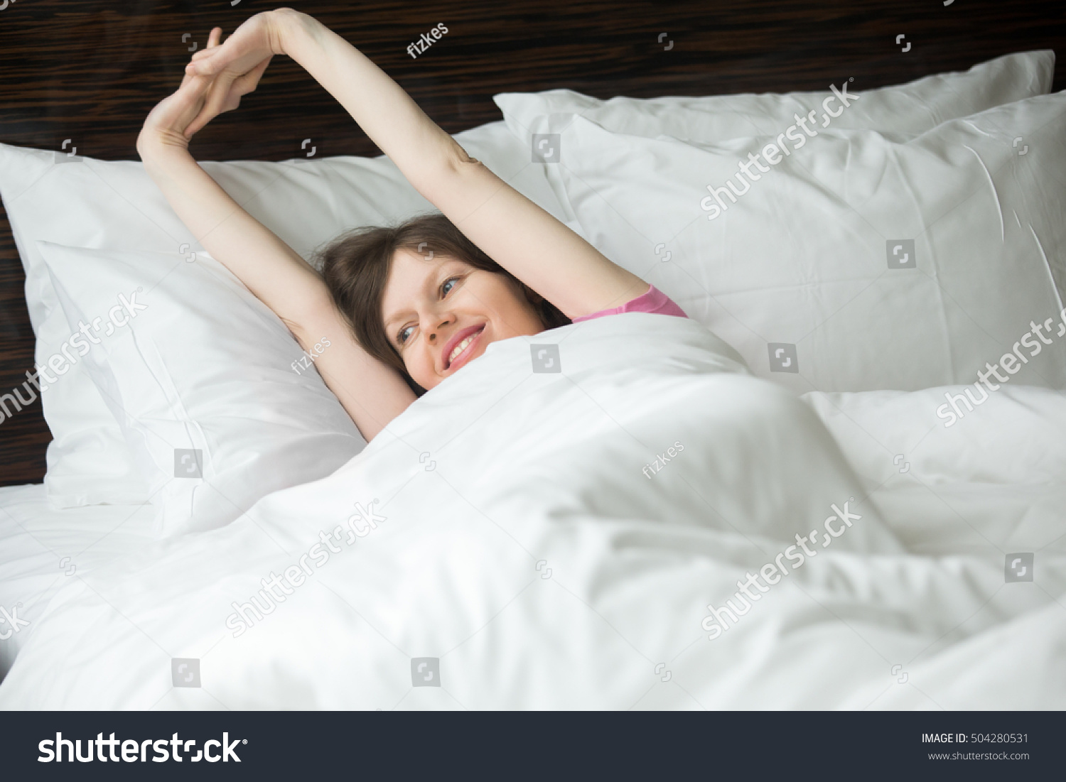 Portrait Of Happy Young Woman Lying In Bed After Waking Up And Stretching  After Good Night