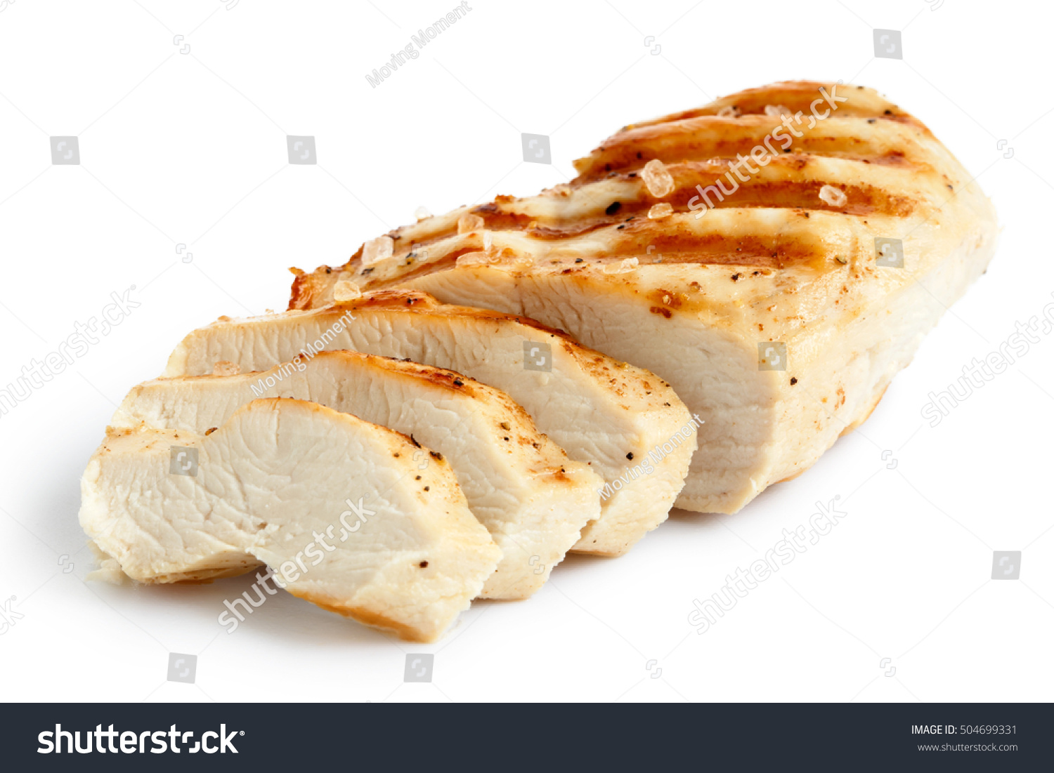 Partially sliced grilled chicken breast with black pepper and rock salt isolated on white. #504699331
