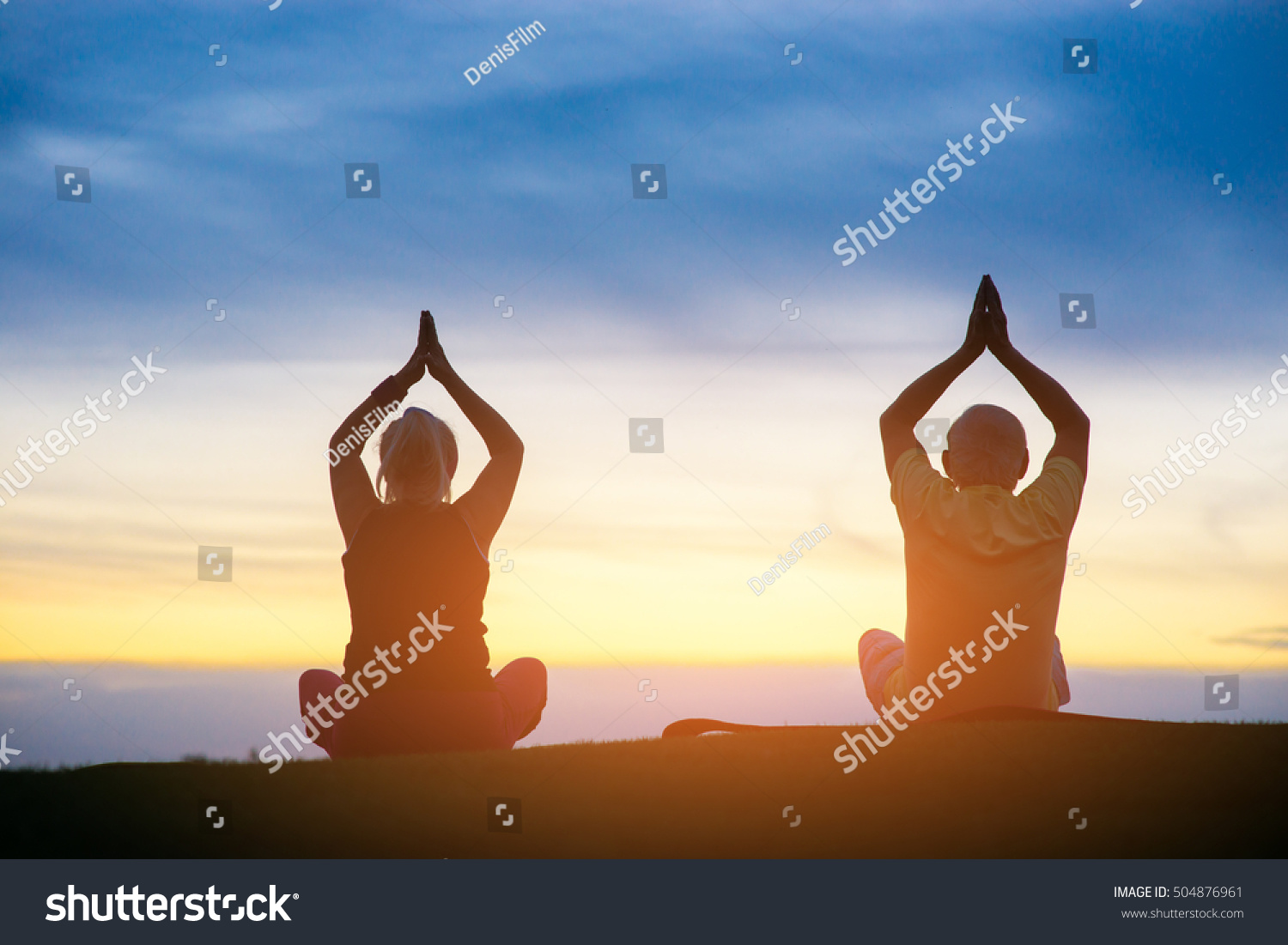 Silhouette of couple doing yoga People sitting on sunset background Eternal search of harmony Mind and body