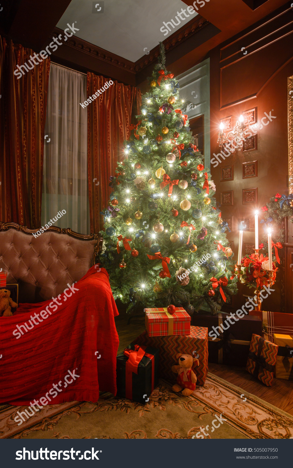 Christmas evening by candlelight classic apartments with a white fireplace decorated tree sofa large windows and chandelier