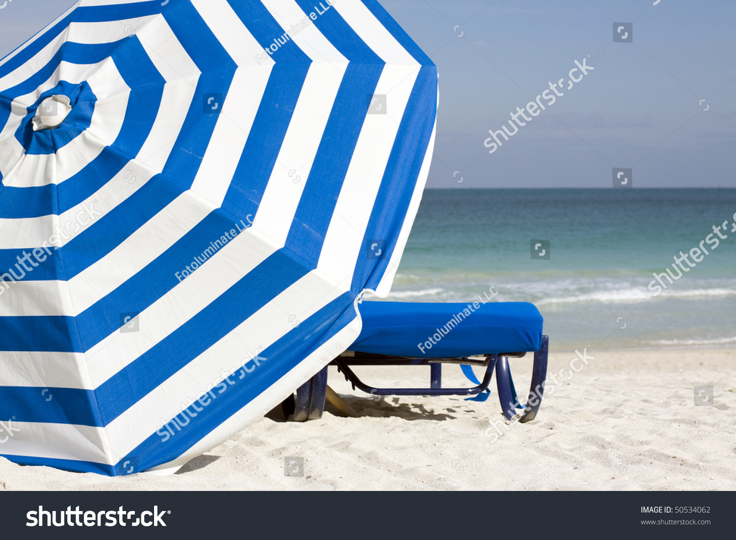 Beach chair and umbrella set - Image Of Blue Lounge Chair And Blue And White Striped Umbrella Set Against The South Beach