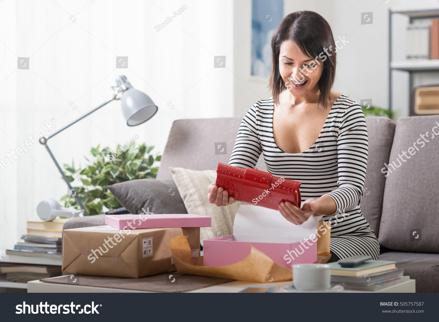 Happy woman unboxing a parcel containing a fashion bag online shopping delivery and customer satisfaction concept