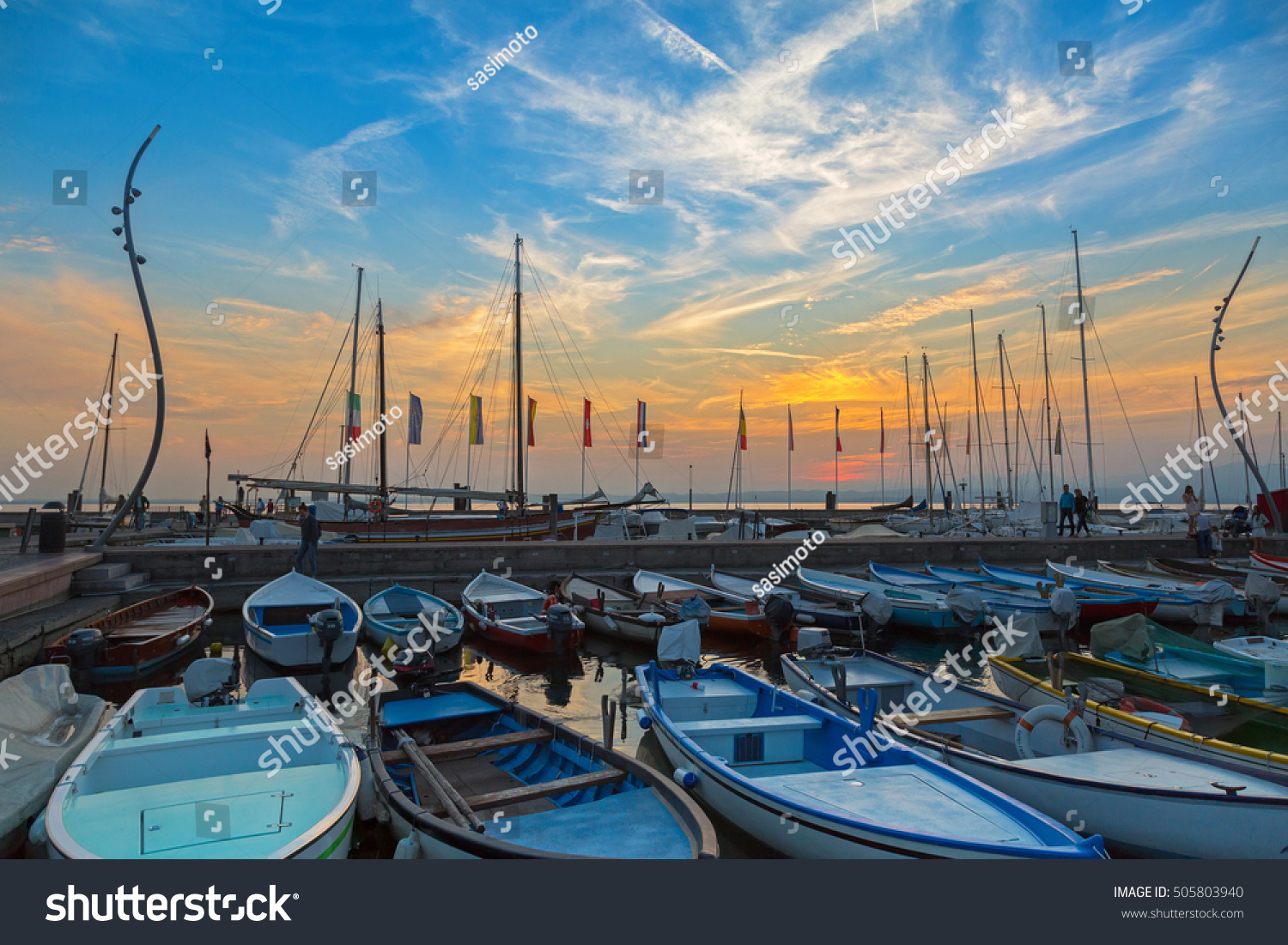 LAKE GARDA ITALY SEPTEMBER 2016 Sailboats fishing boats at Porto di Bardolino harbor on The Garda Lake during sunset in Italy on September 24 2016 It is largest lake in Italy