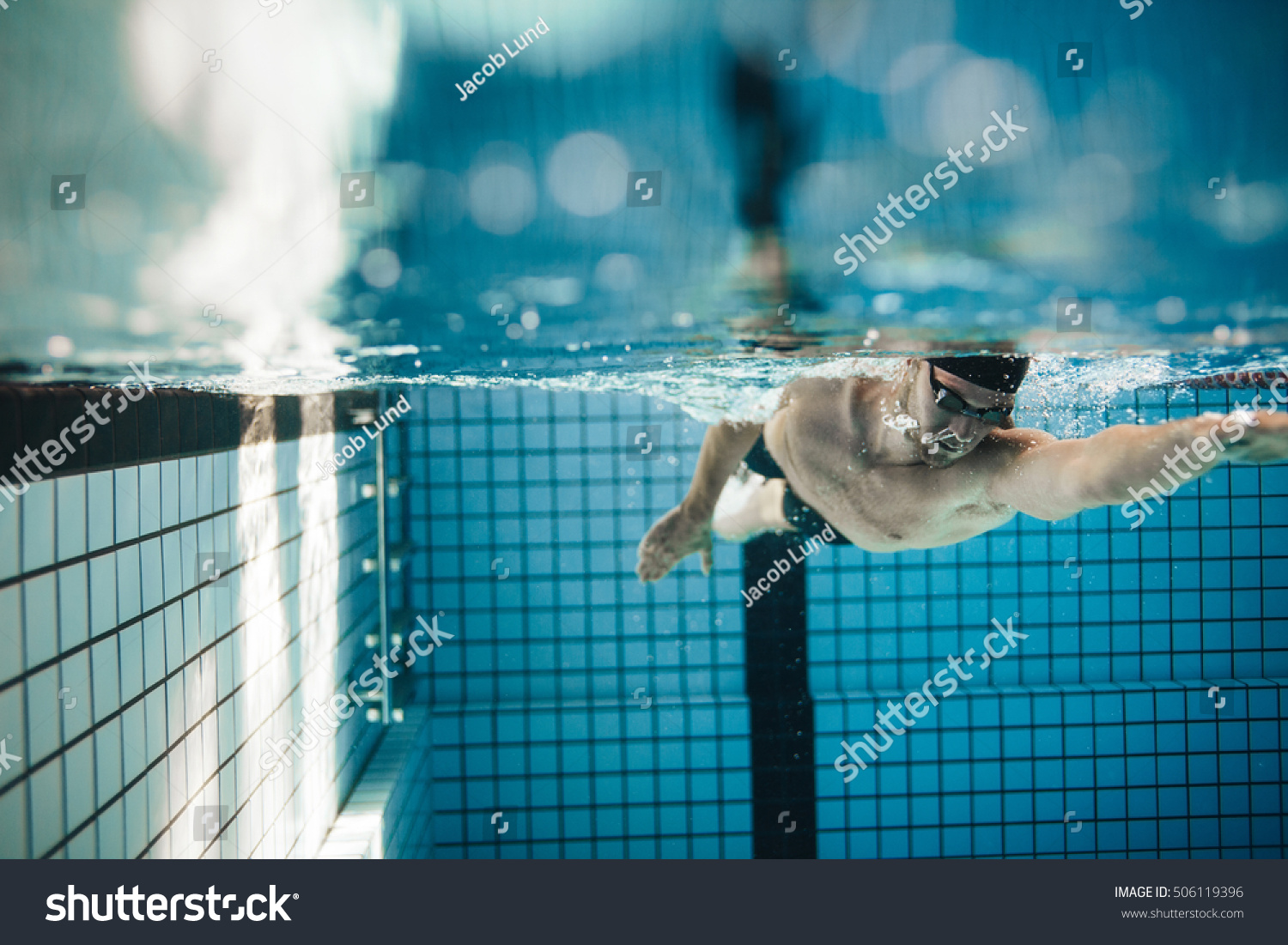 Swimming Pool Action : Fit young male swimmer training pool stock photo