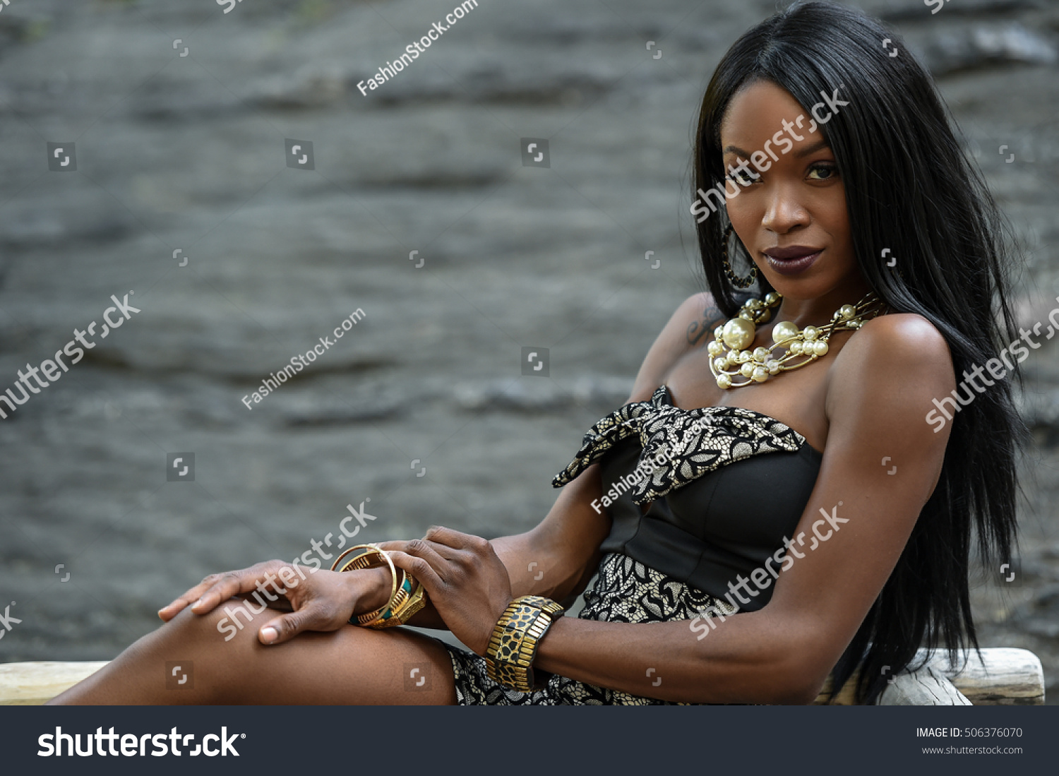 235c3befefb Exotic looking African American woman posing in front of camera wearing  black mini dress and jewellery