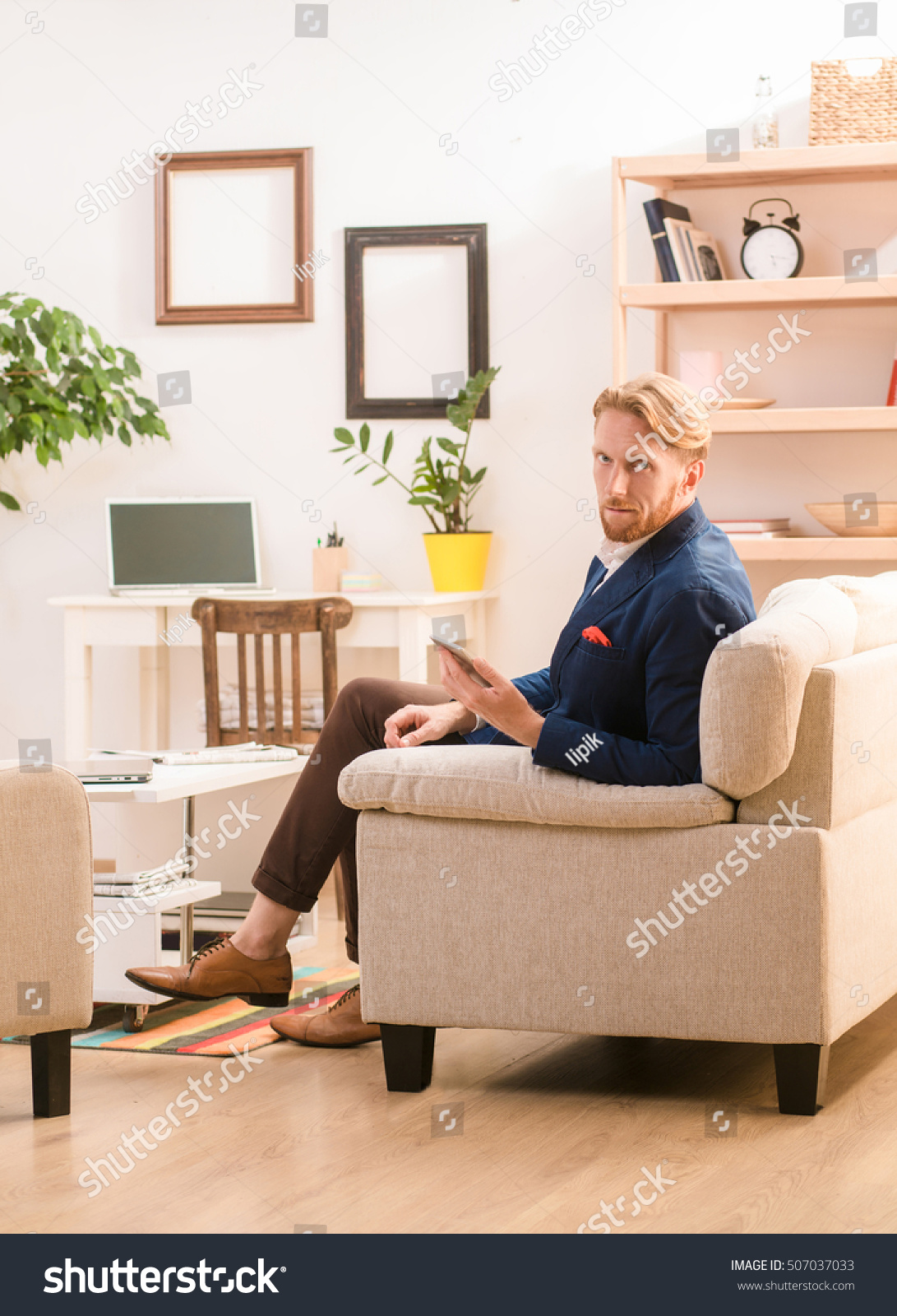 portrait serious confident blond european businessman stock photo portrait of serious and confident blond european businessman staying at home sitting on sofa or
