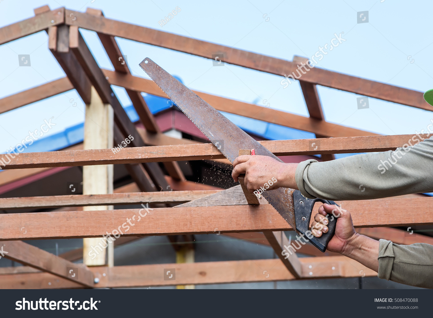 Close Up Of Carpenter S Hands Sawing House Roof Supports