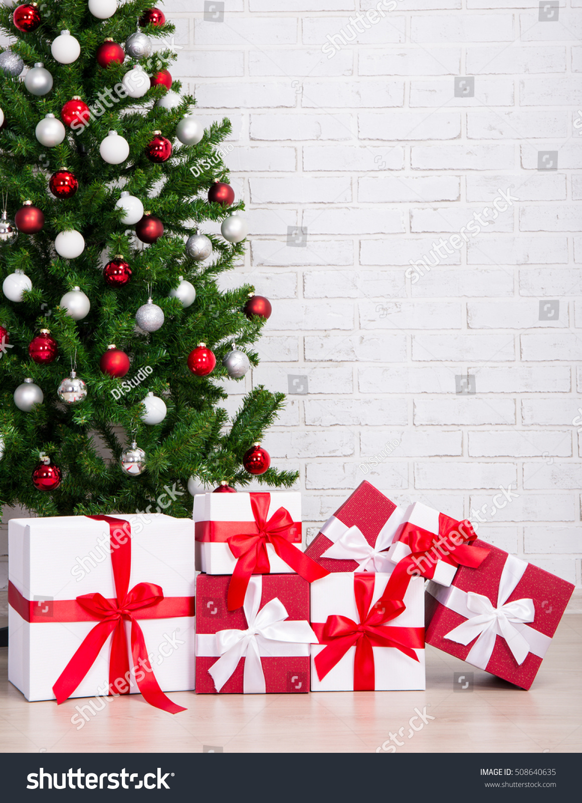 Gift boxes under decorated christmas tree with colorful balls over white brick wall