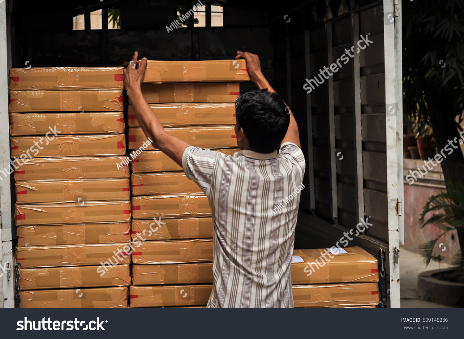 Royalty-free A courier man loading materials in a… #509148286 Stock