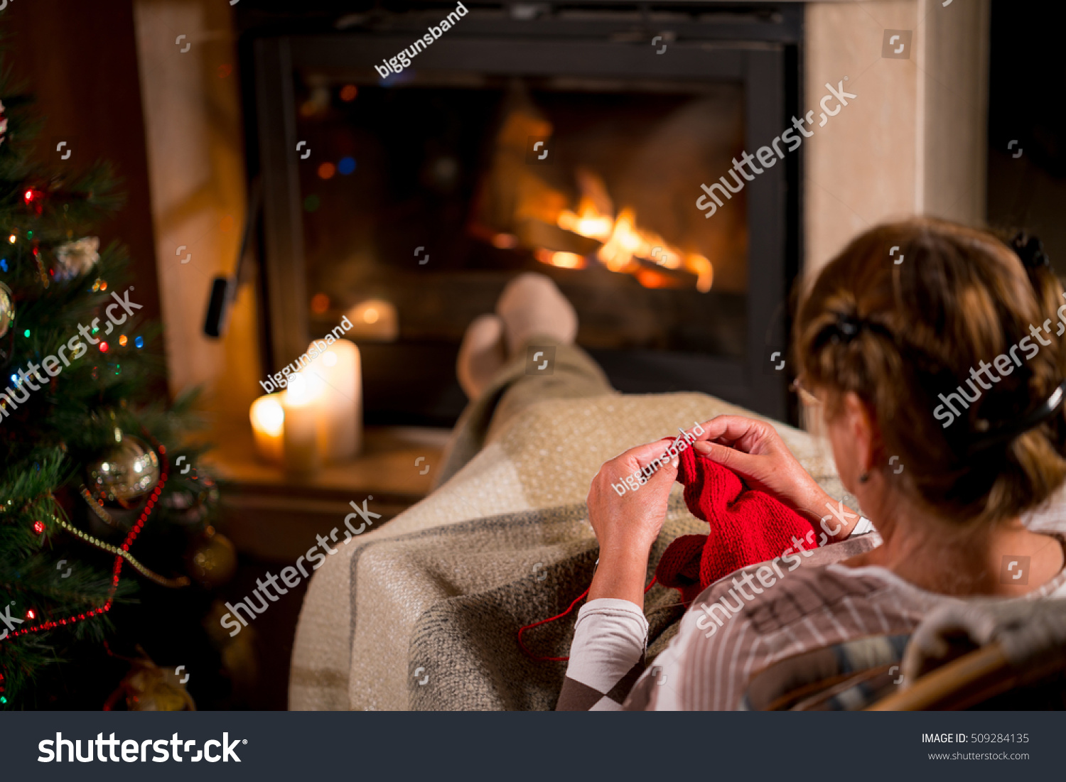 grandmother knits sweater sitting front fireplace stock photo