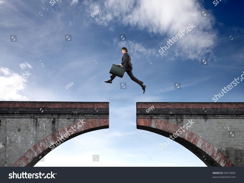 Businessman Jumping Gap Between Two Bridge Stock Photo