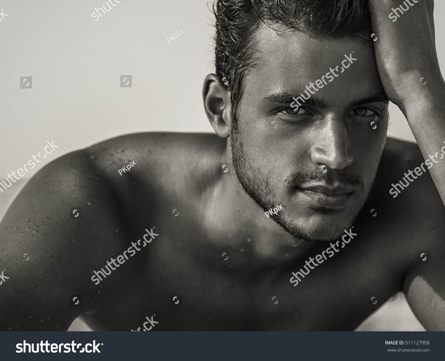 Sexy closeup portrait of handsome topless male model with beautiful eyes on the beach black
