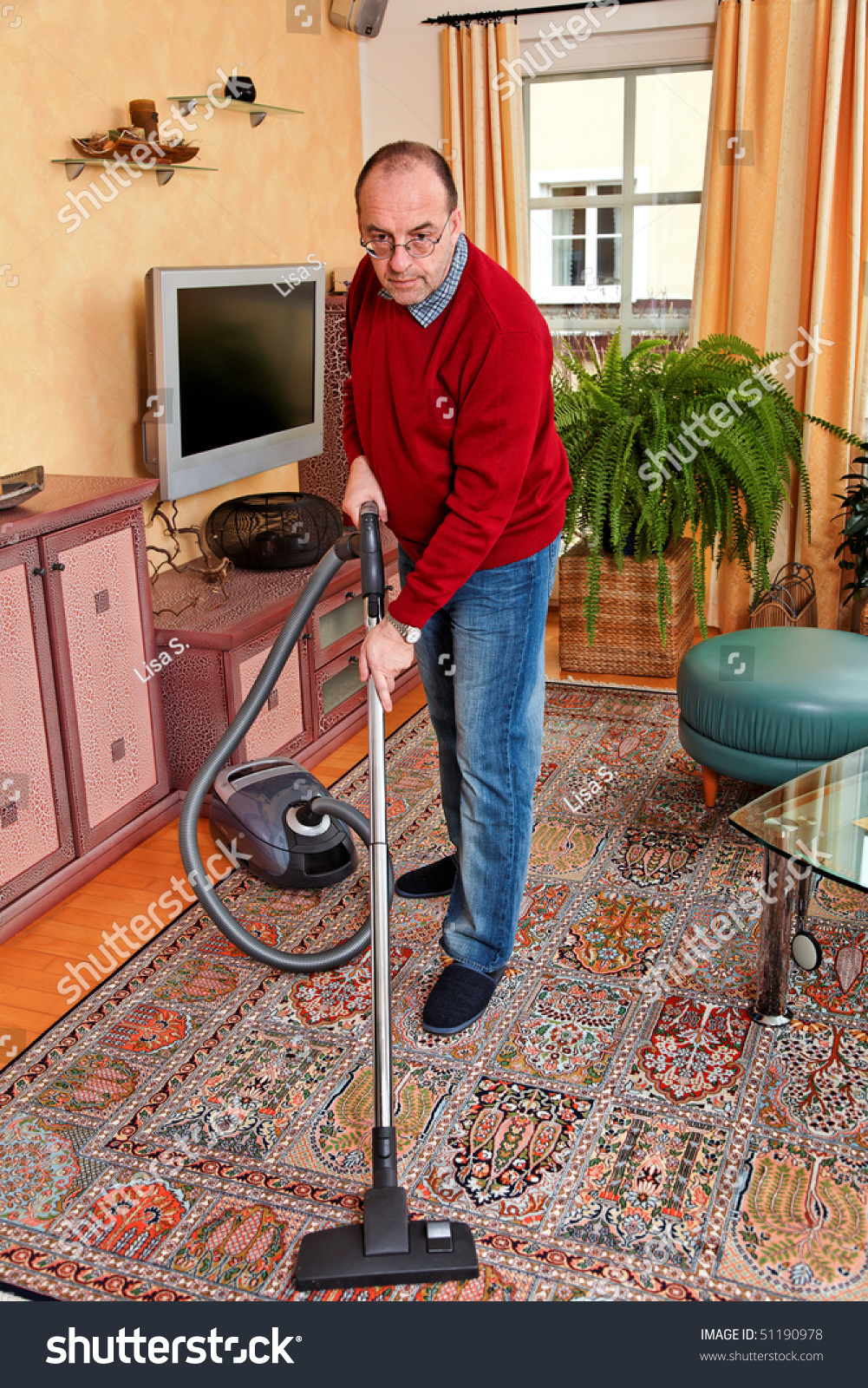 man cleans the apartment with a vacuum cleaner housework