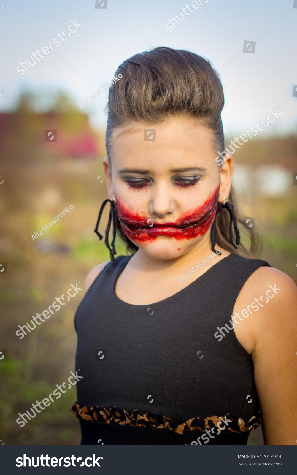 girl halloween applying makeup scary makeup stock photo (edit now