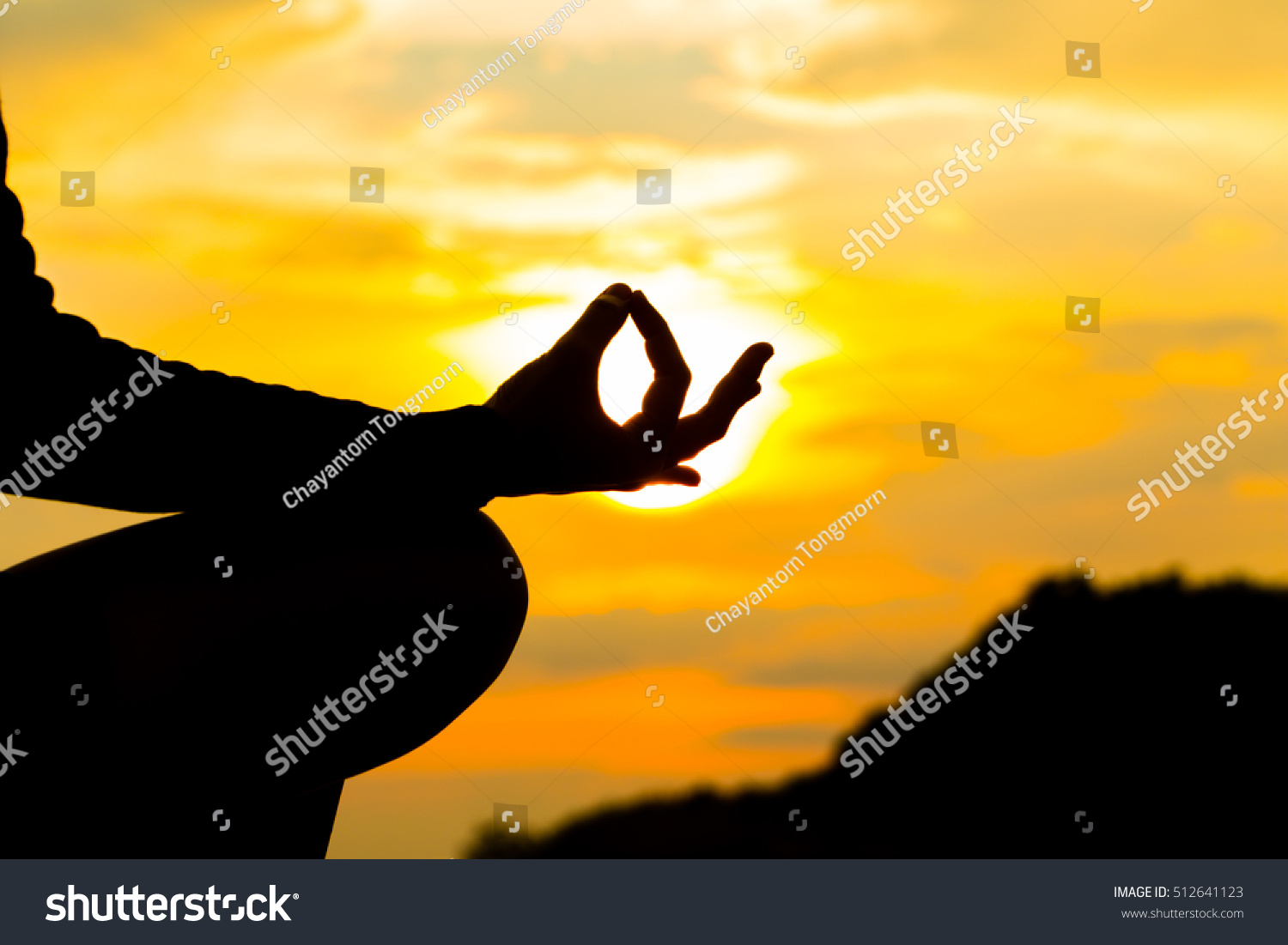 Silhouette Hand Of Woman Meditating In Yoga Pose Or Lotus Position By The Sea At