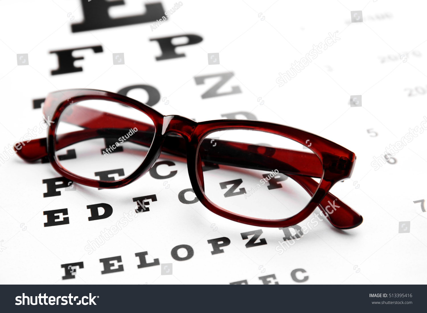 Glasses lying on eye test chart stock photo 513395416 shutterstock glasses lying on eye test chart close up view healthy eyes concept geenschuldenfo Image collections