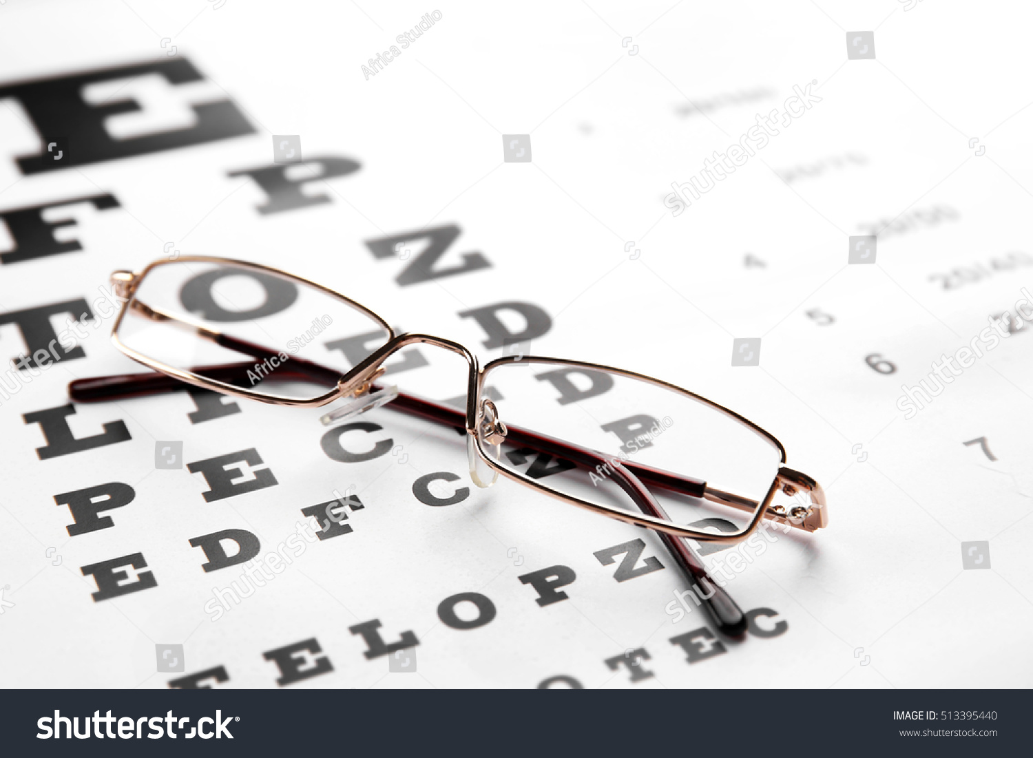 Glasses lying on eye test chart stock photo 513395440 shutterstock glasses lying on eye test chart close up view healthy eyes concept geenschuldenfo Image collections