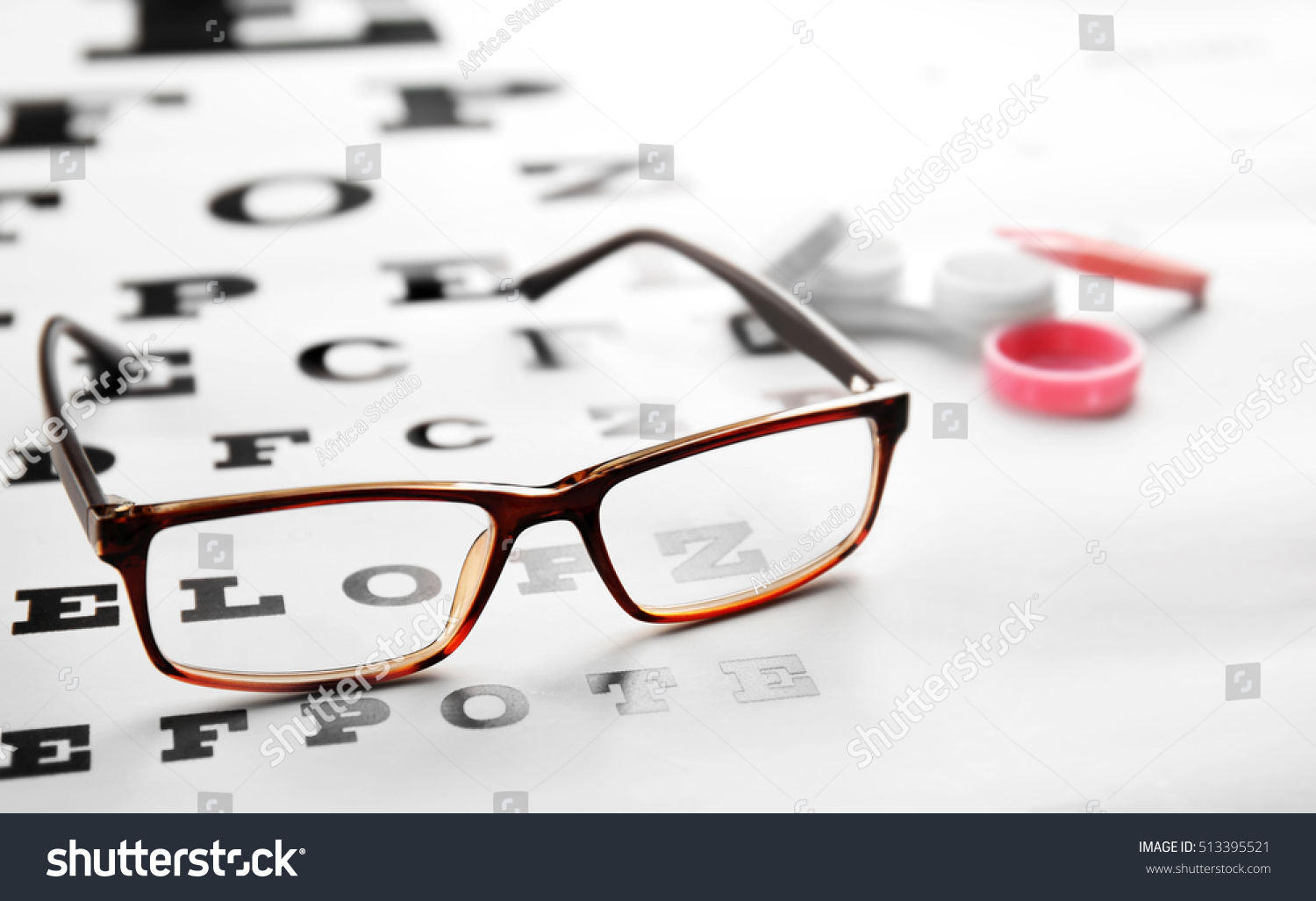 Glasses lying on eye test chart stock photo 513395521 shutterstock glasses lying on eye test chart close up view healthy eyes concept geenschuldenfo Image collections