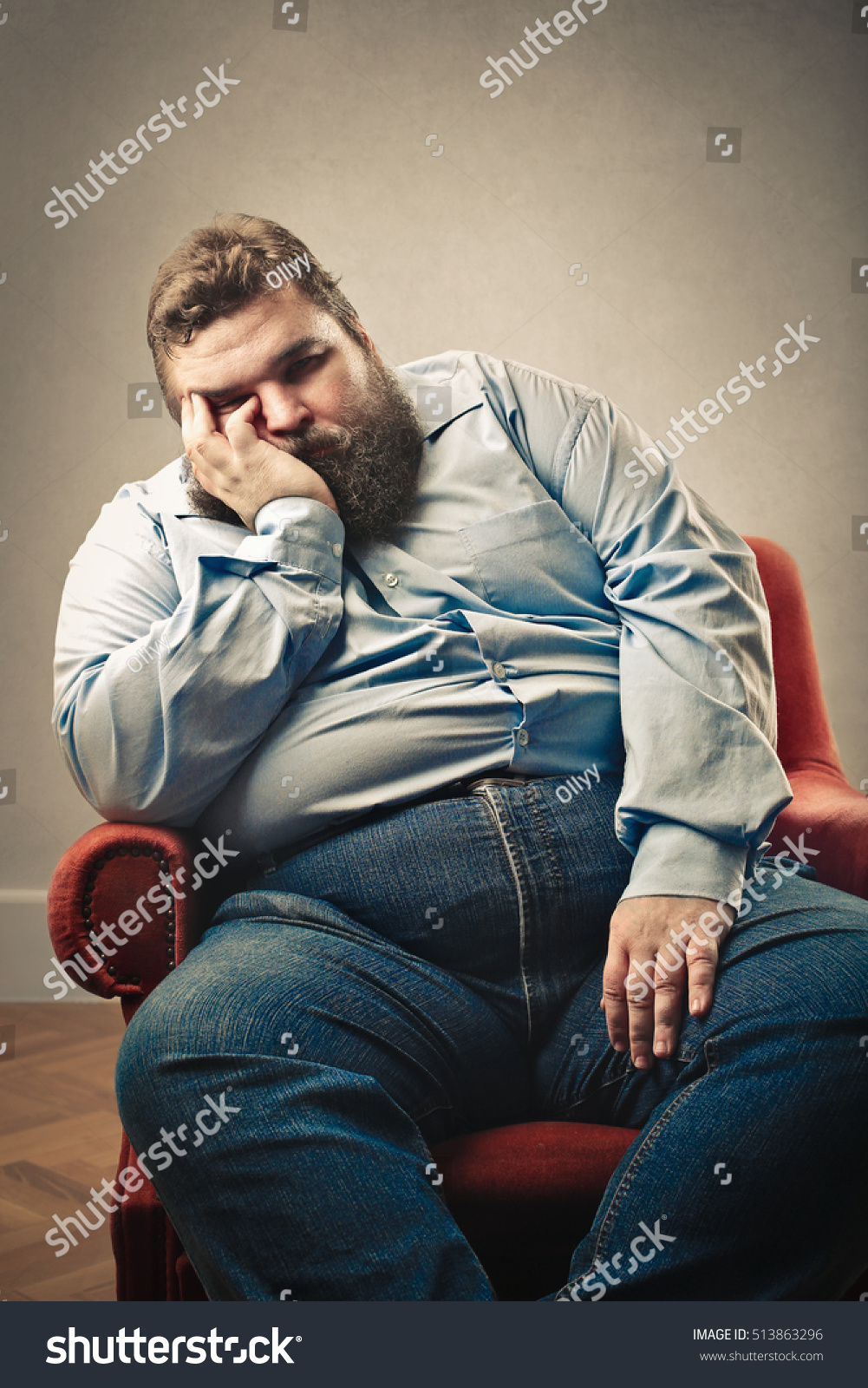 Obese man sitting in a red armchair stock photo 513863296 for Sitting in armchair