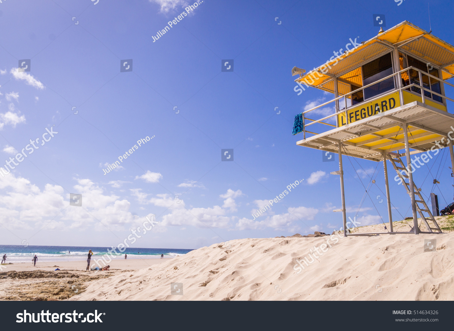 3c61563b55e Yellow lifeguard tower watching over beach with blue sky at Snapper Rocks