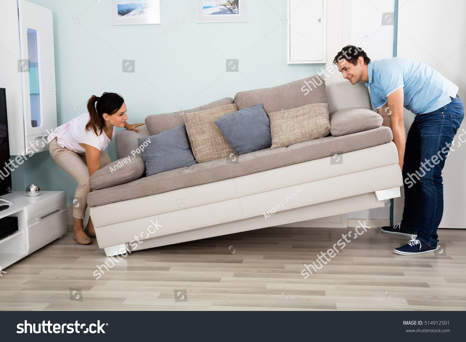 Young happy couple placing sofa together stock photo for Living room ideas for young couples