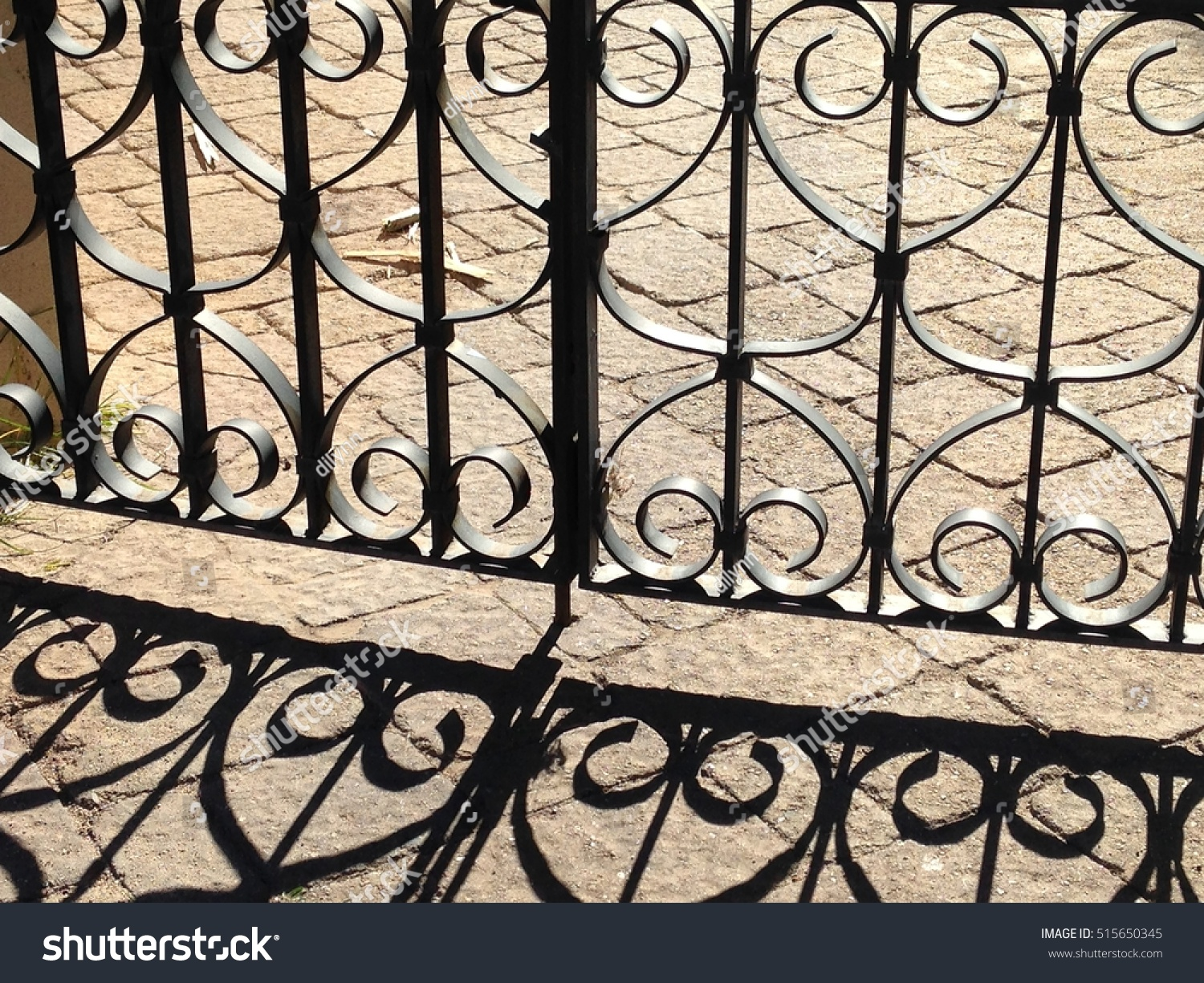 Ornate wrought iron fence throwing shadow stock photo