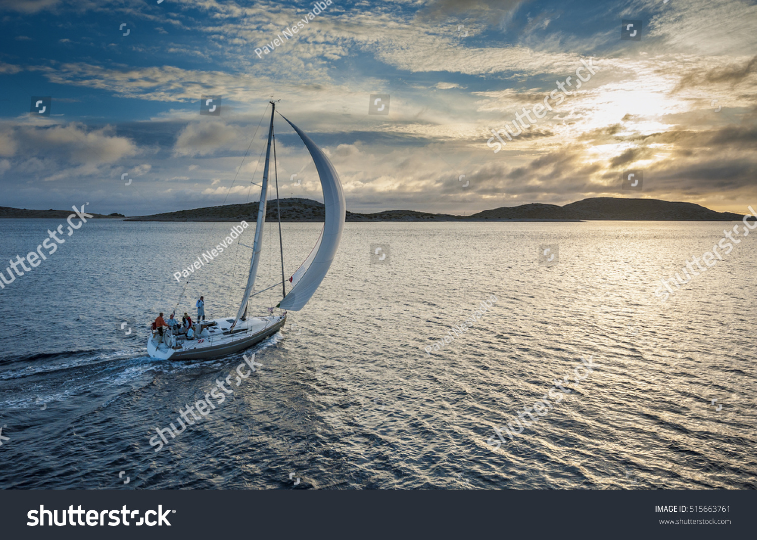 Sailing boat with spinnaker sail on open sea #515663761