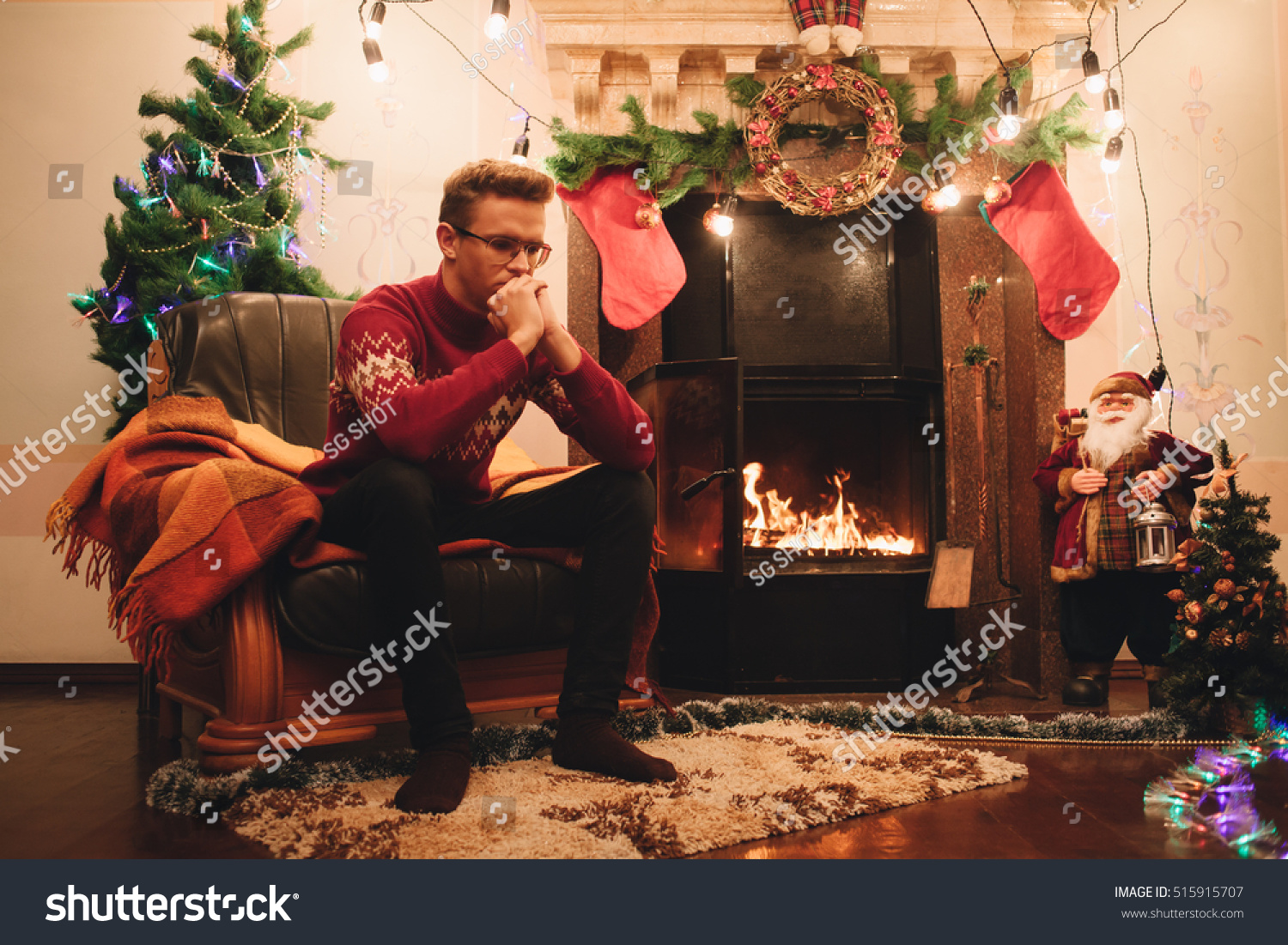 man red sweater sitting front fireplace stock photo 515915707