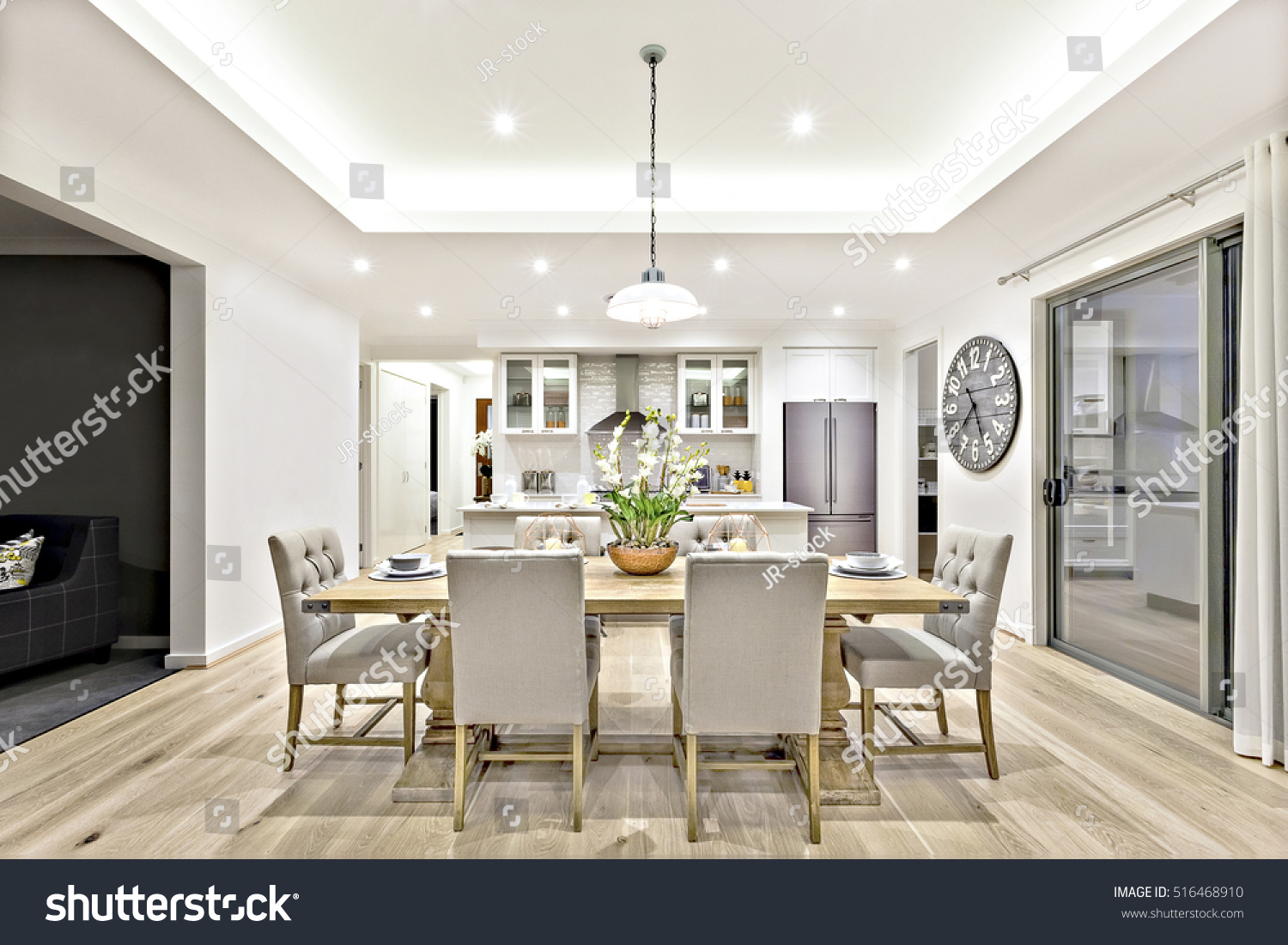 Modern Dining Room With Hanging Lamps On, There Are Chairs And Table Setup  With Fancy