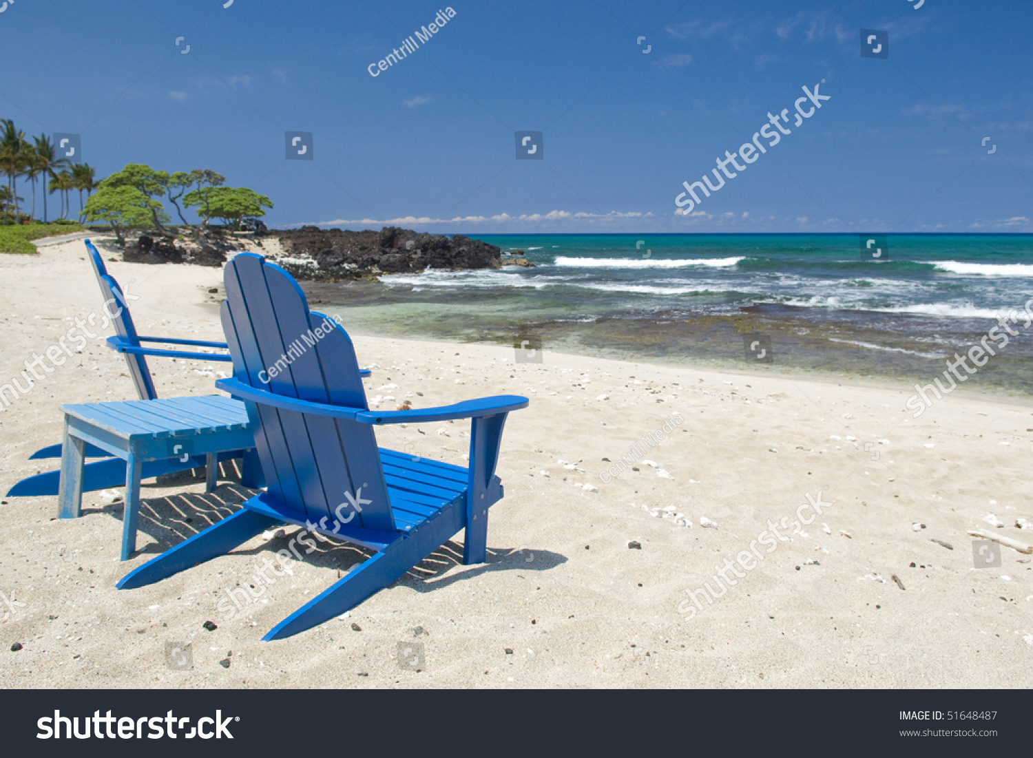 Style chairs sit on a hawaiian beach facing the pacific ocean