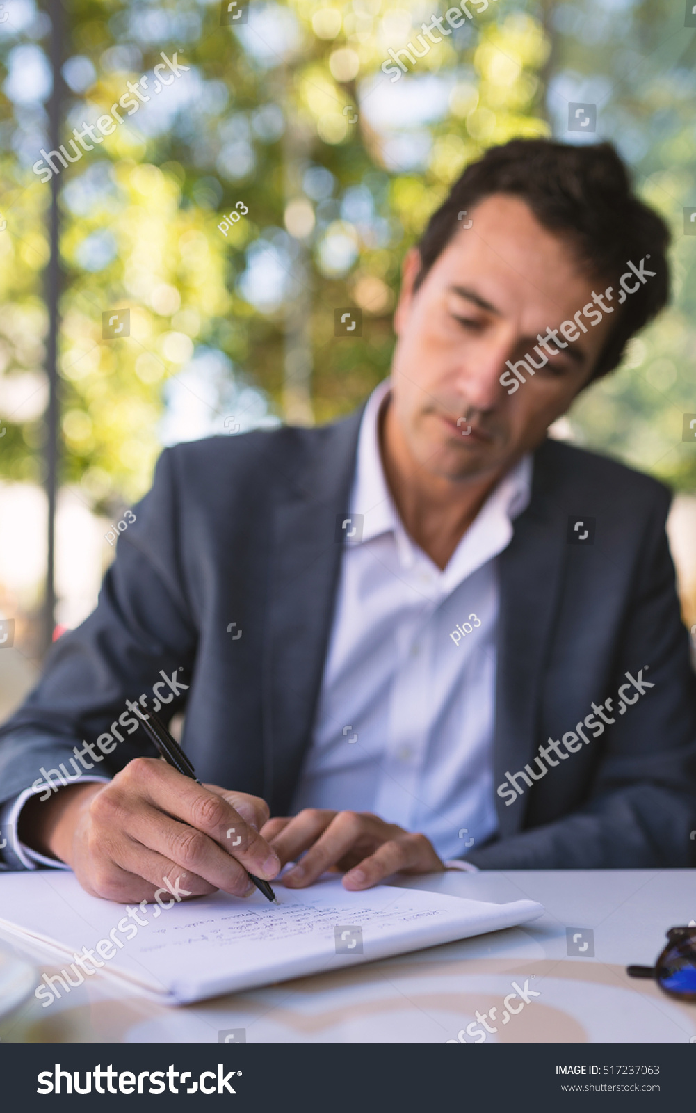 concentrate middle age businessman portrait writing stock photo concentrate middle age businessman portrait writing an essay outdoors in rome focus on