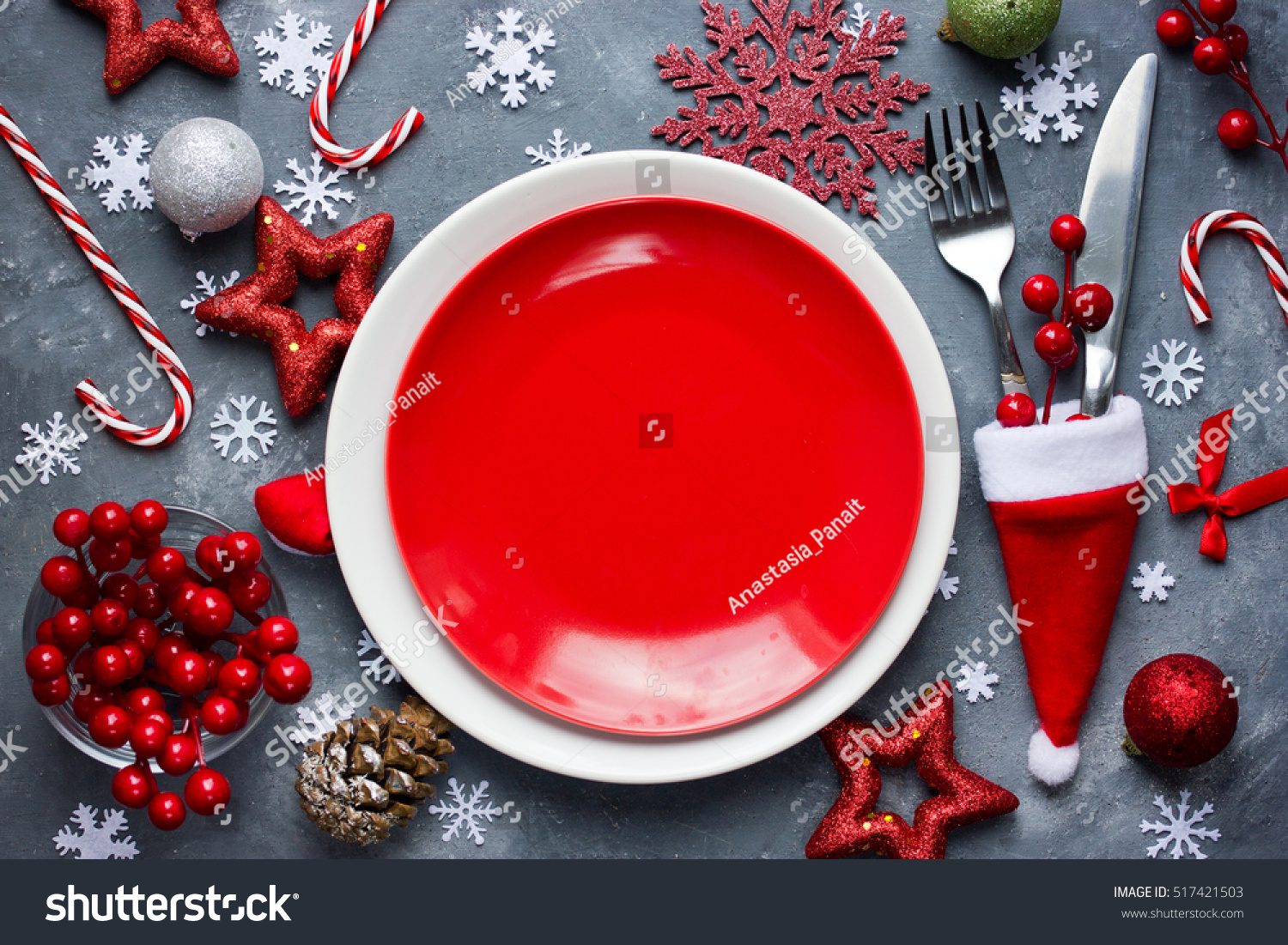 christmas table place setting with empty red plate cutlery in santa hat with festive decorations - Candy Cane Christmas Table Decorations