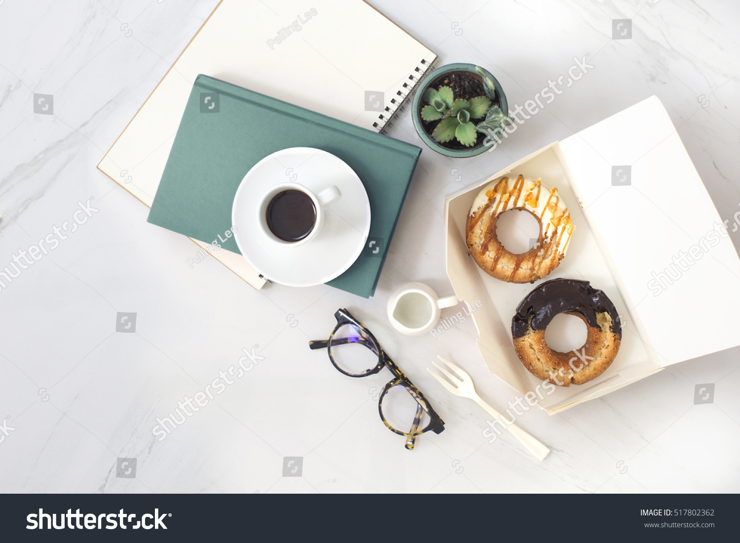 Overhead view of chocolate cake donuts with salted caramel glaze with a cup of espresso on marble table top Afternoon me time book reading with dessert and coffee Text space images