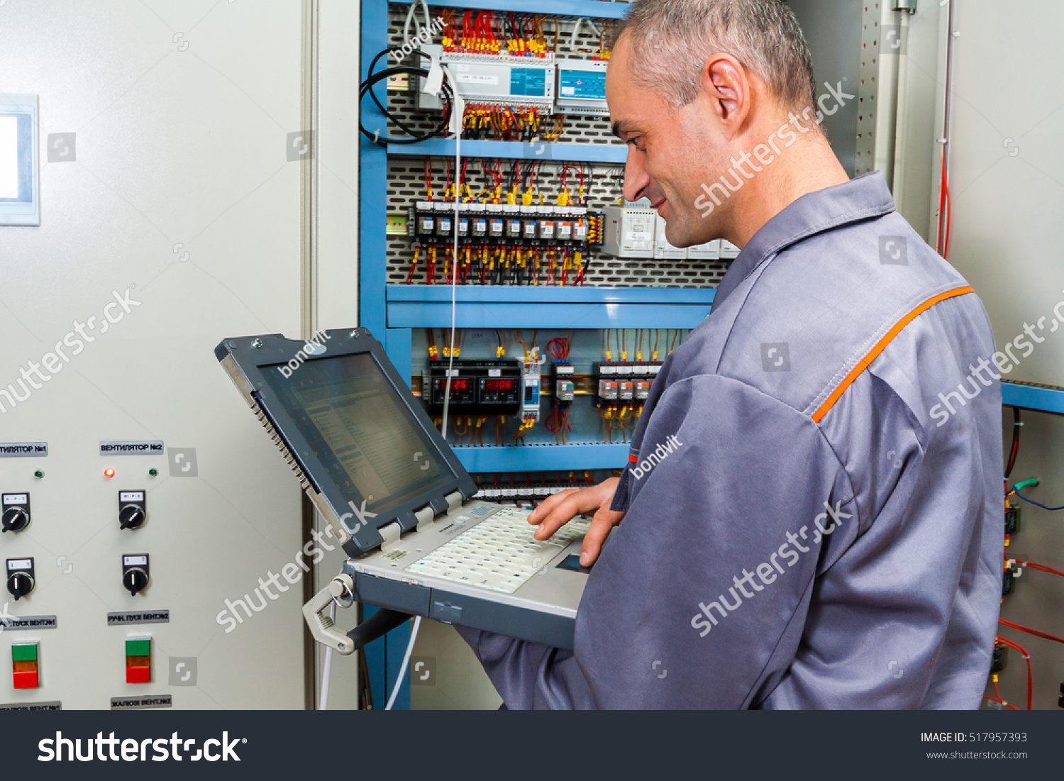 Electrician Builder Engineer Screwing Testing Equipment Stock Photo Industrial Fuse Box And In Machine Repairing