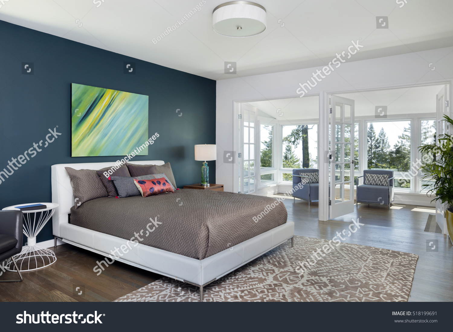 Open spacious bedroom with modern stylish furniture and double french doors. Open Spacious Bedroom Modern Stylish Furniture Stock Photo