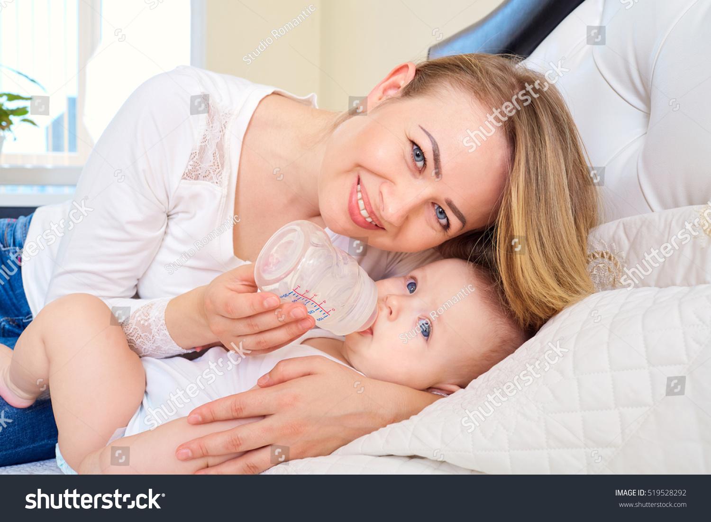 mom feeding her baby bottle bed stock photo 519528292 - shutterstock