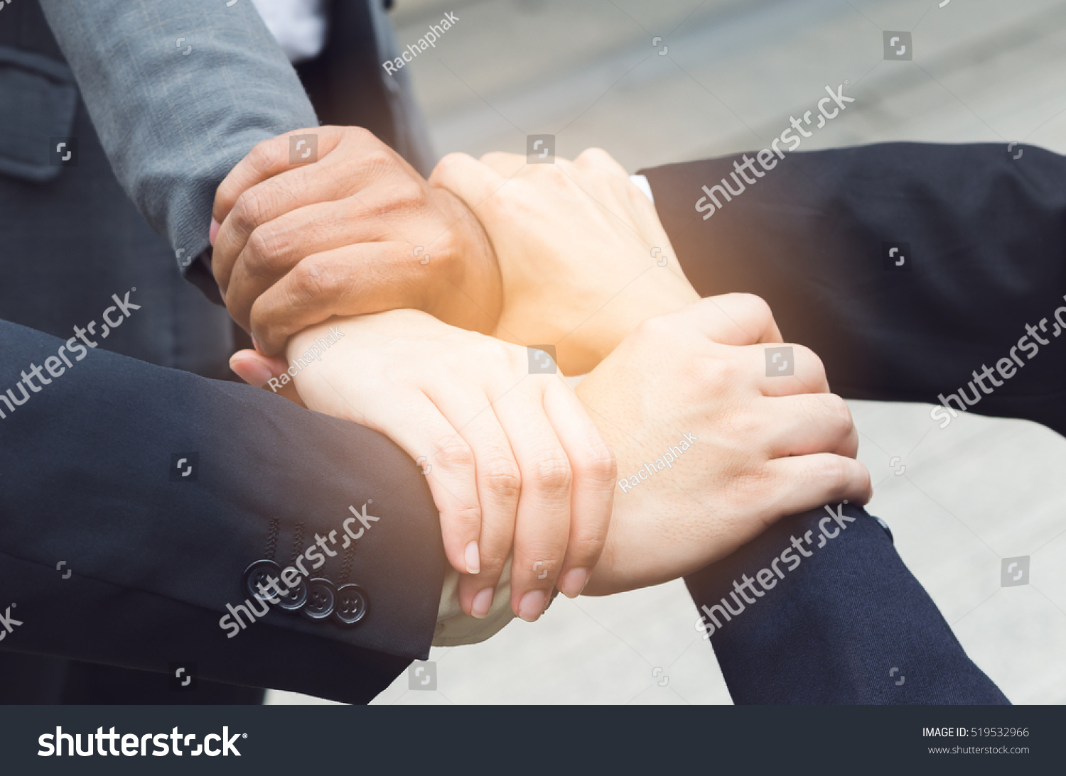 Four business man and women holding hand together
