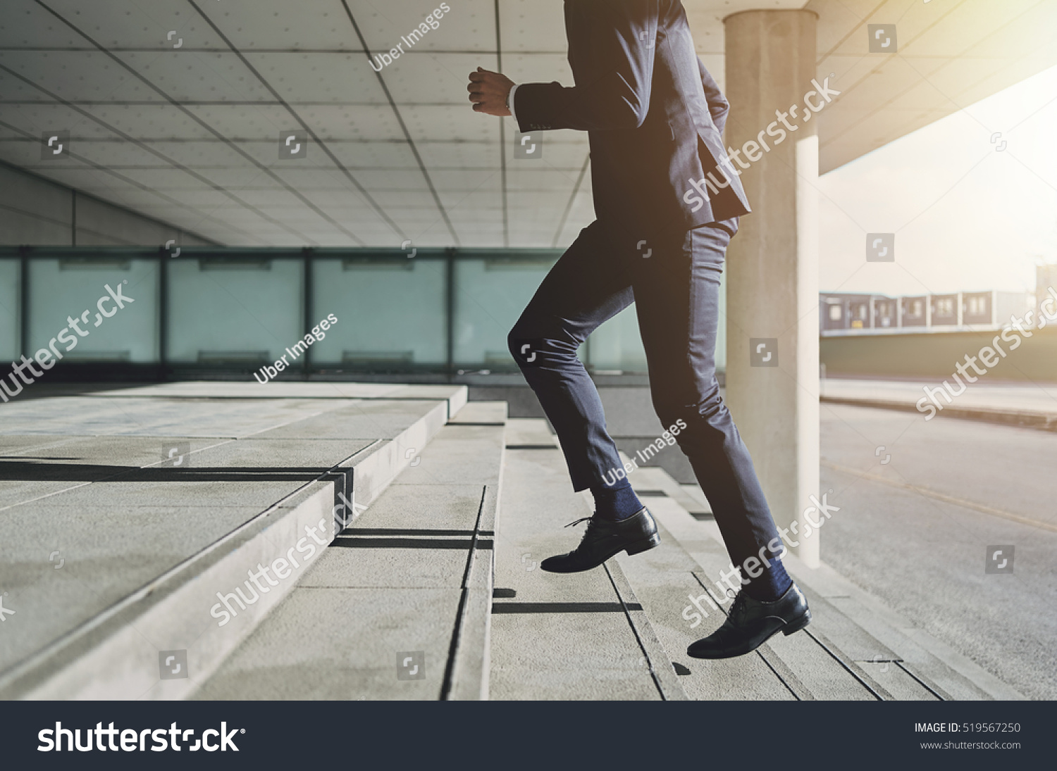 Businessman running fast upstairs. Horizontal outdoors shot. #519567250